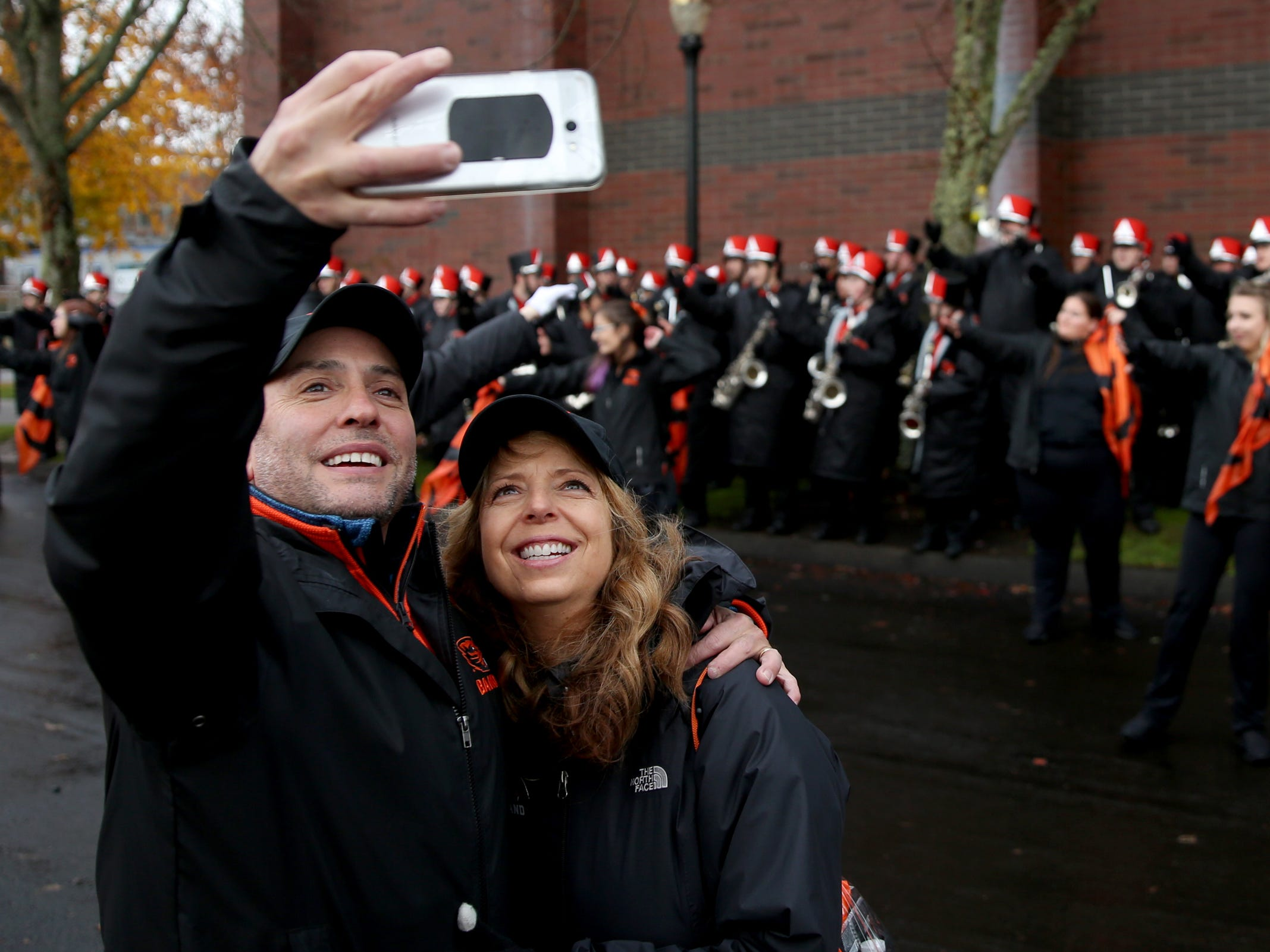 Dennis and Shelly Childers, of Medford, take a photo together with their daughter in the background before the start of the Oregon vs. Oregon State Civil war football game at Oregon State University in Corvallis on Friday, Nov. 23, 2018. Their daughter, Ryleigh Childers, is in the Oregon State marching band.