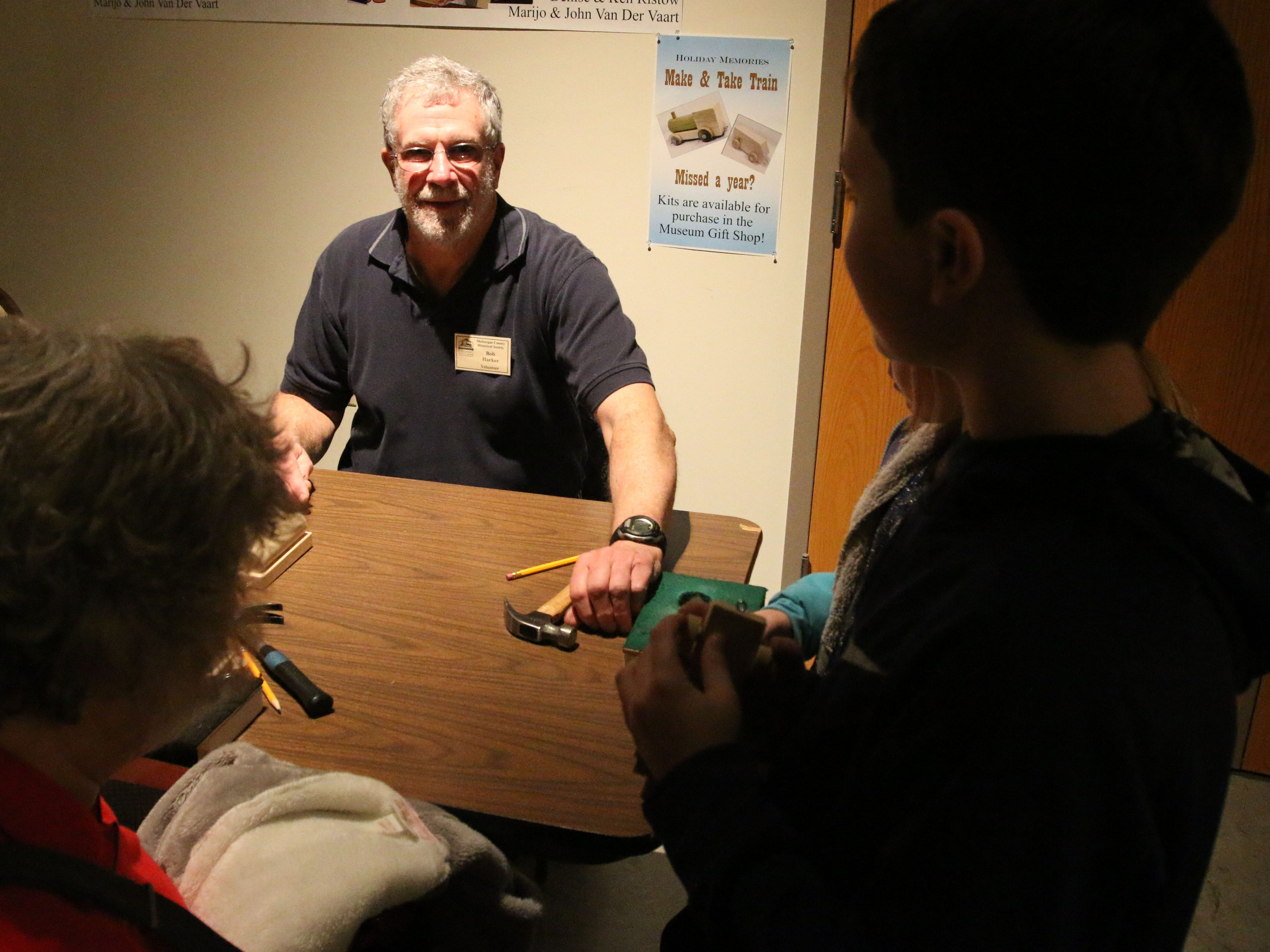 Museum volunteer Bob Harker greets children at a hands on toy workshop for children at the Sheboygan County Historical Museum's Holiday Memories, Friday, November 23, 2018, in Sheboygan, Wis.