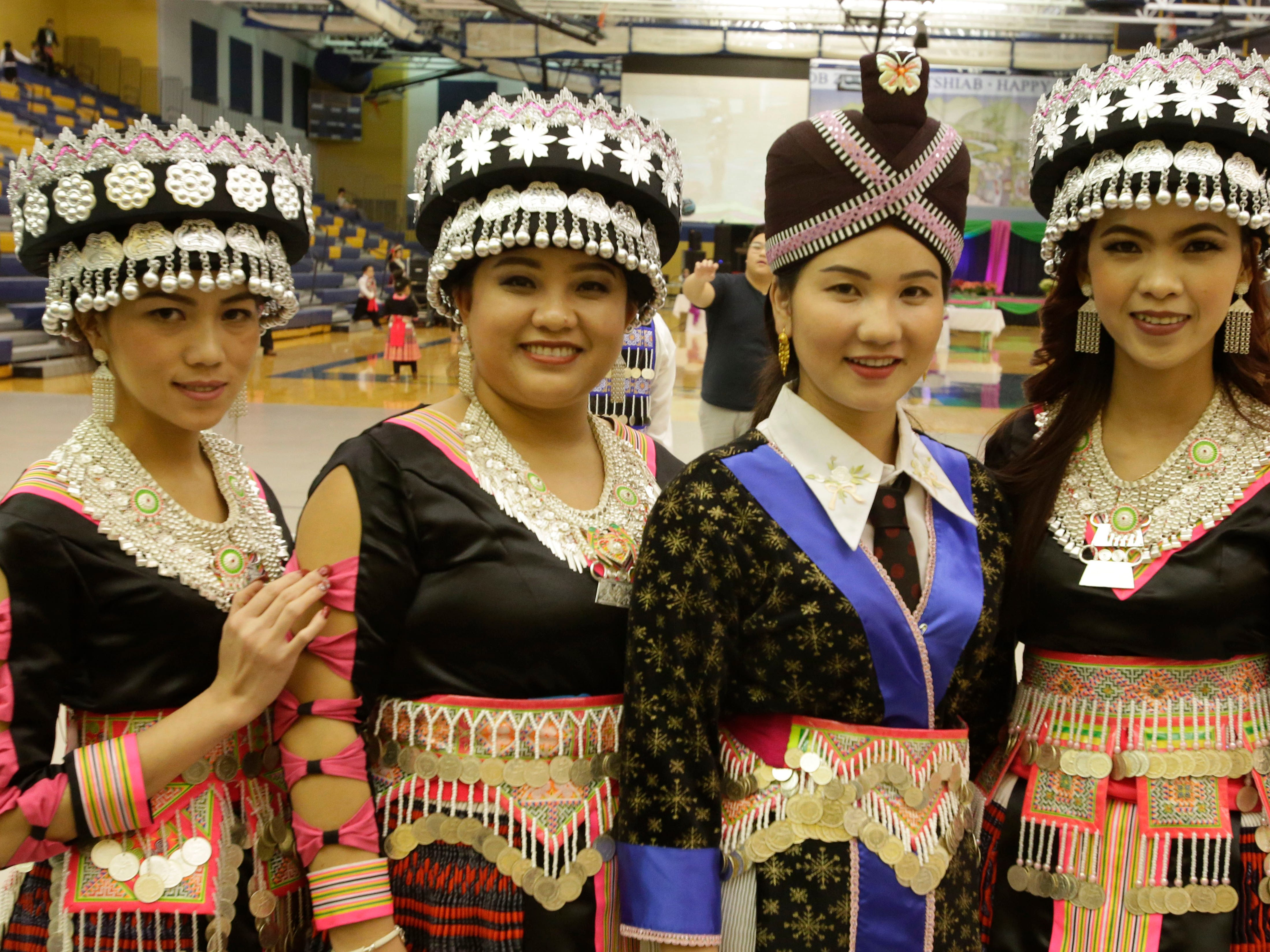 A quartet of young Hmong women pose for a photo at the Hmong New Year observance at Sheboygan North High School, Friday, November 23, 2018, in Sheboygan, Wis.