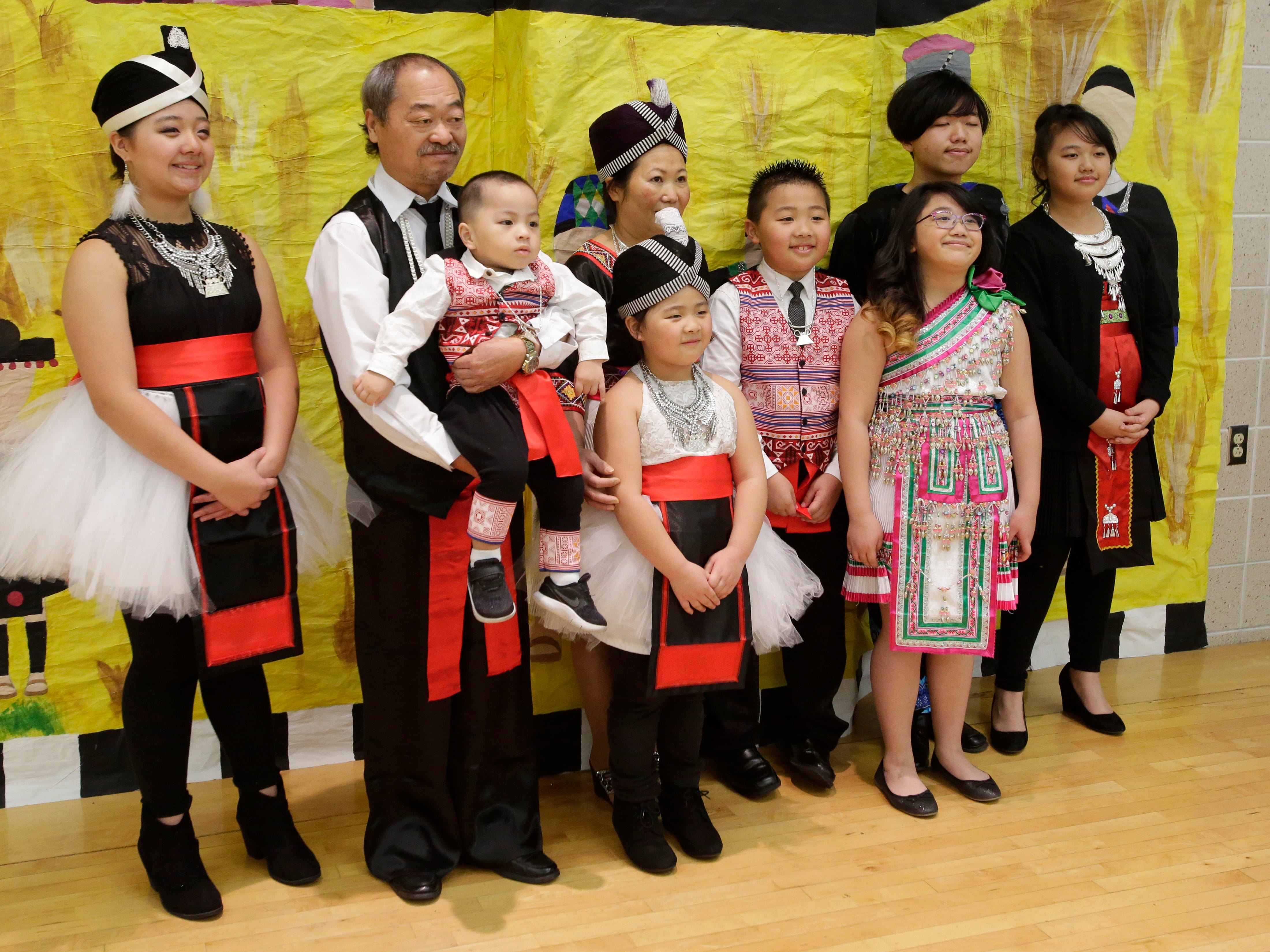 A Hmong family poses for cameras at the Hmong New Year observance at Shebygan North High School, Friday, November 23, 2018, in Sheboygan, Wis.