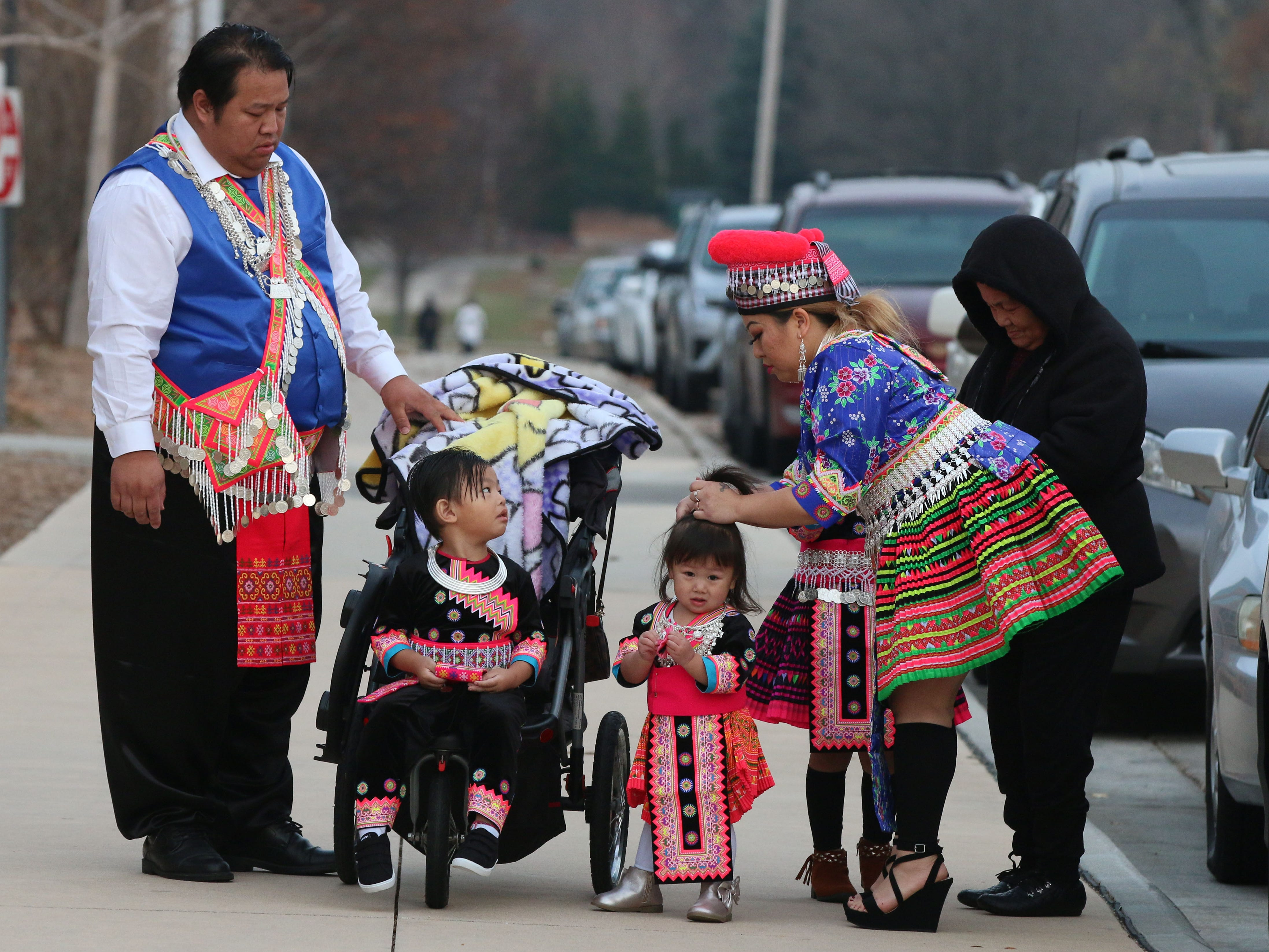 A Hmong family prepares their outfits before entering the Hmong New Year Celebration at Sheboygan North High School, Friday, November 23, 2018, in Sheboygan, Wis.