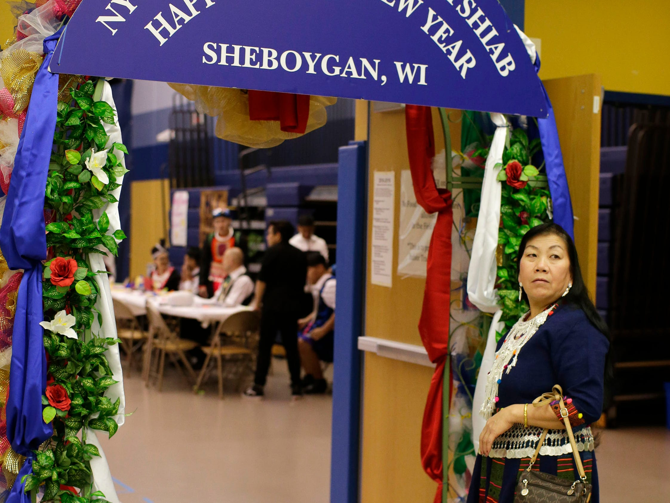 A Hmong woman stands near the entrance to the Hmong New Year at Sheboygan North High School, Friday, November 23, 2018, in Sheboygan, Wis.