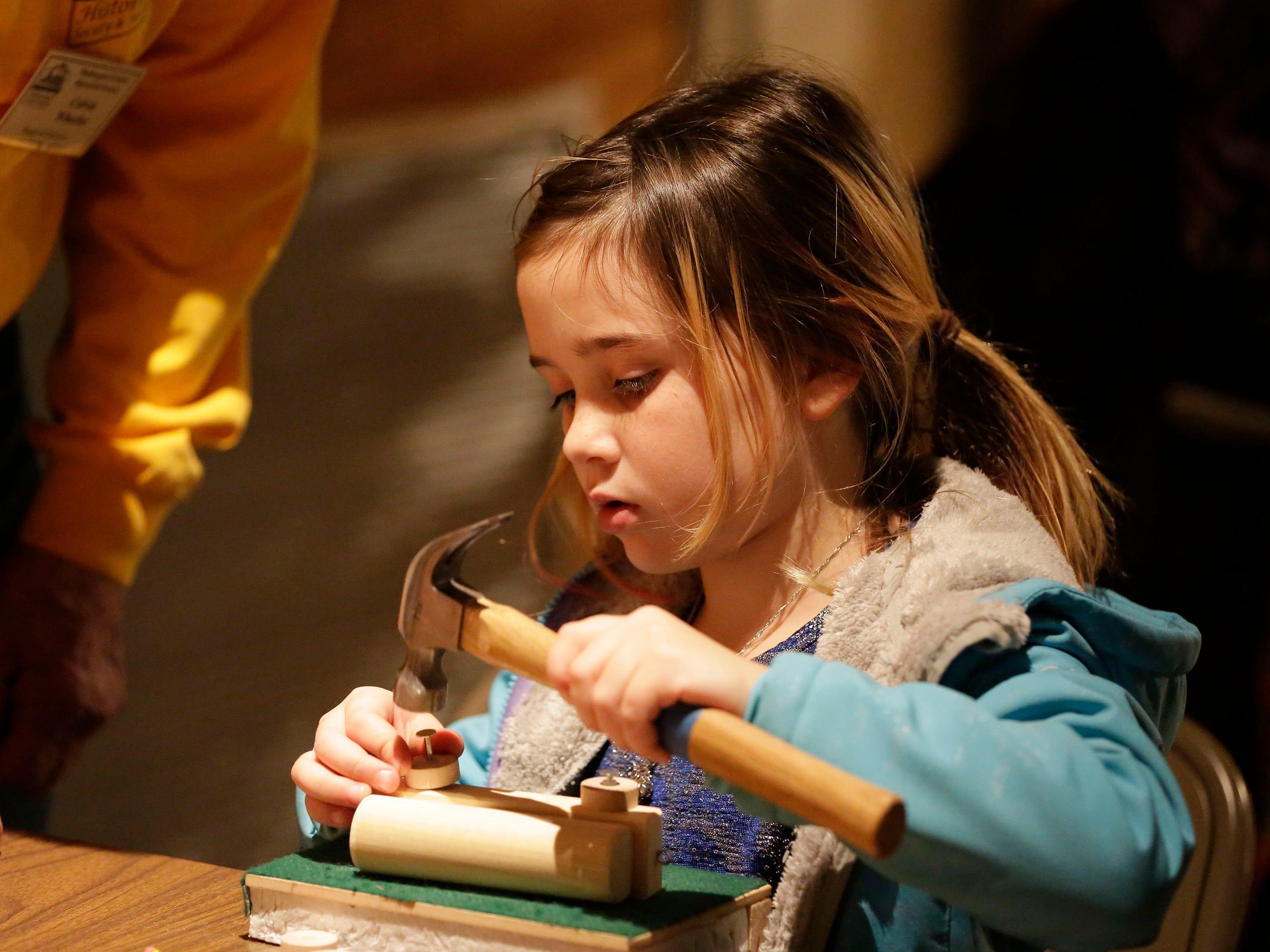 Leora Hurtado, 8, of Spring Green, Wis., creates a toy at a workshop at the Sheboygan County Historical Museum's Holiday Memories, Friday, November 23, 2018, in Sheboygan, Wis.