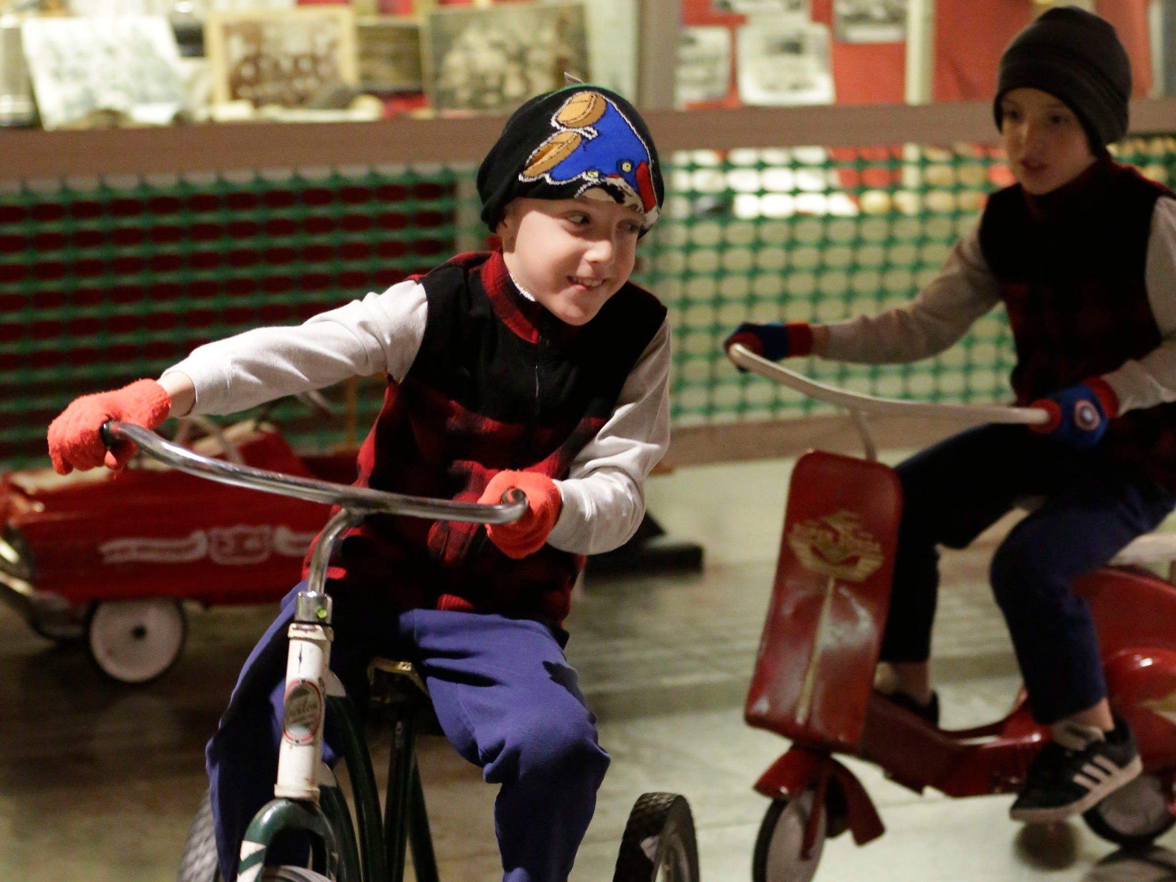 Bryce Van Auken, 7, of Sheboygan Falls, Wis., pedals a vintage Garton toy ahead of his twin brother Nolan, 7, during the Sheboygan County Historical Museum's Holiday Memories, Friday, November 23, 2018, in Sheboygan, Wis.