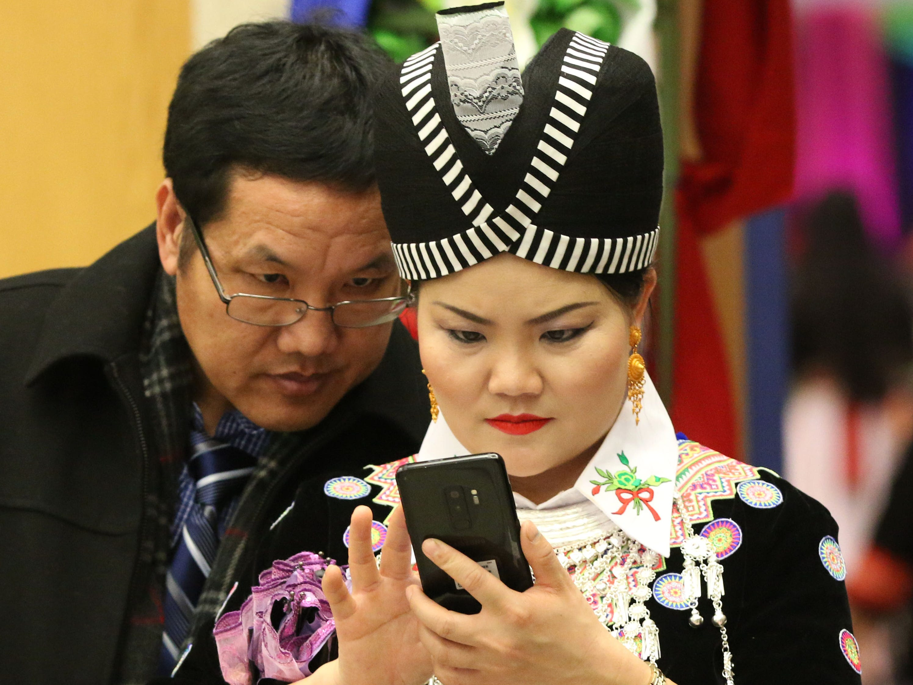 Pao Lee and Pa Houa Xiong, both of Sheboygan, look over photos on Xiong's phone at the Hmong New Year observance at Sheboygan North High School, Friday, November 23, 2018, in Sheboygan, Wis.