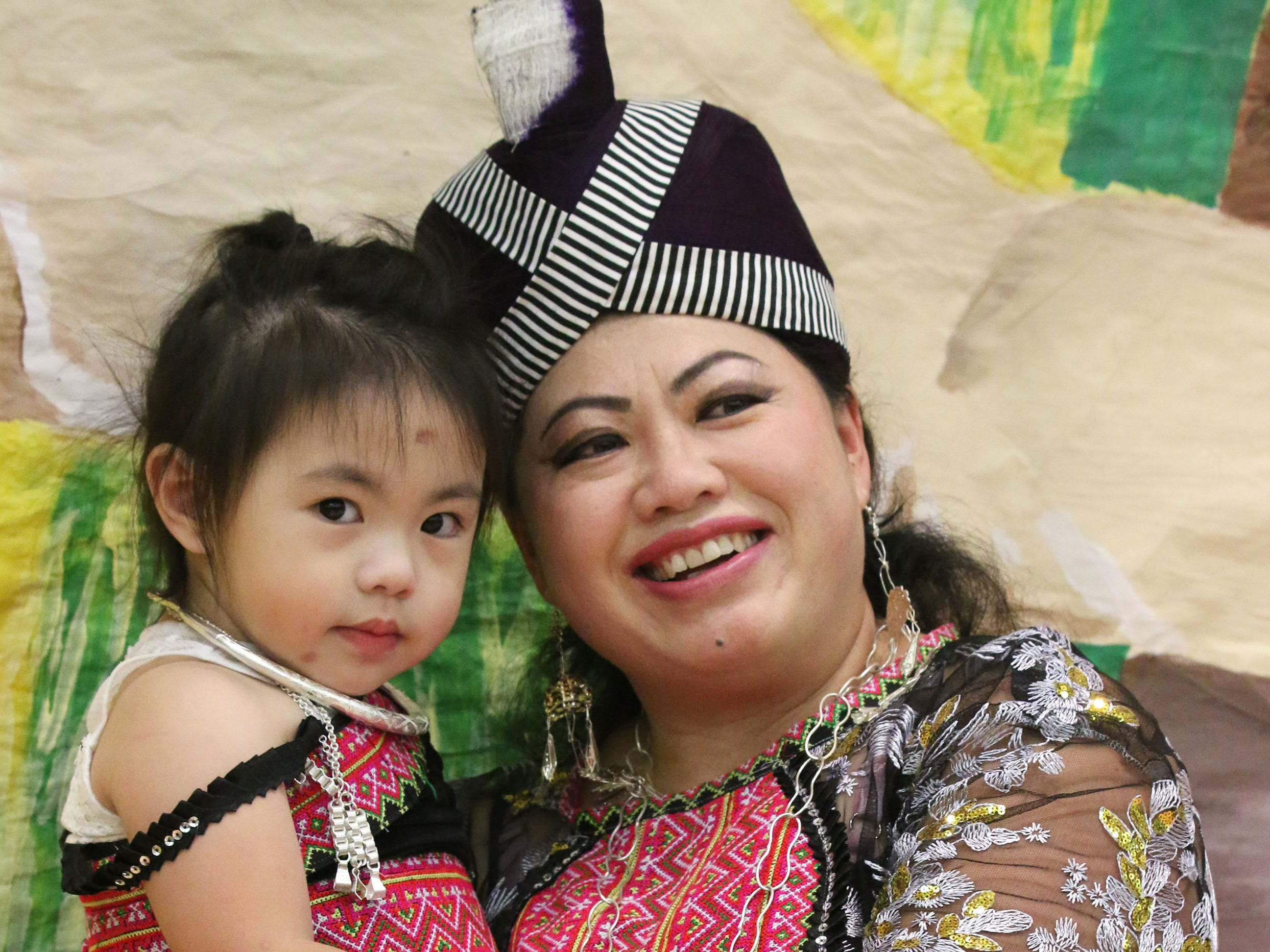 Hui Xianng of Sheboygan holds her daughter Angel Lee, 2, while posing at the Hmong New Year at Sheboygan North High School, Friday, November 23, 2018, in Sheboygan, Wis.