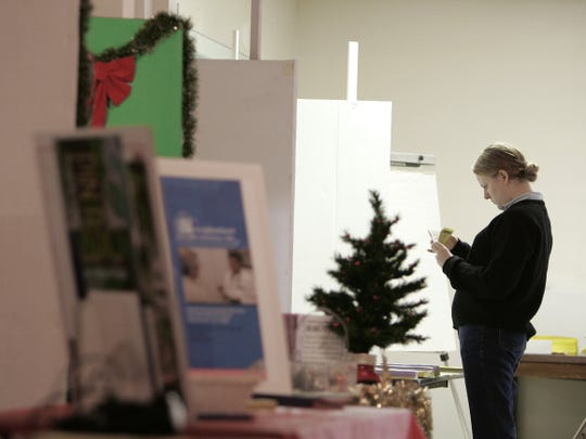 Hope Richardson, a volunteer at the John Wesley United Methodist Church on Old St Augustine Road, organizes items on one of the tables in preparation for the Alternative Christmas Market in 2005. Next weekend, Dec. 1-2, will be the 32nd year for the market.