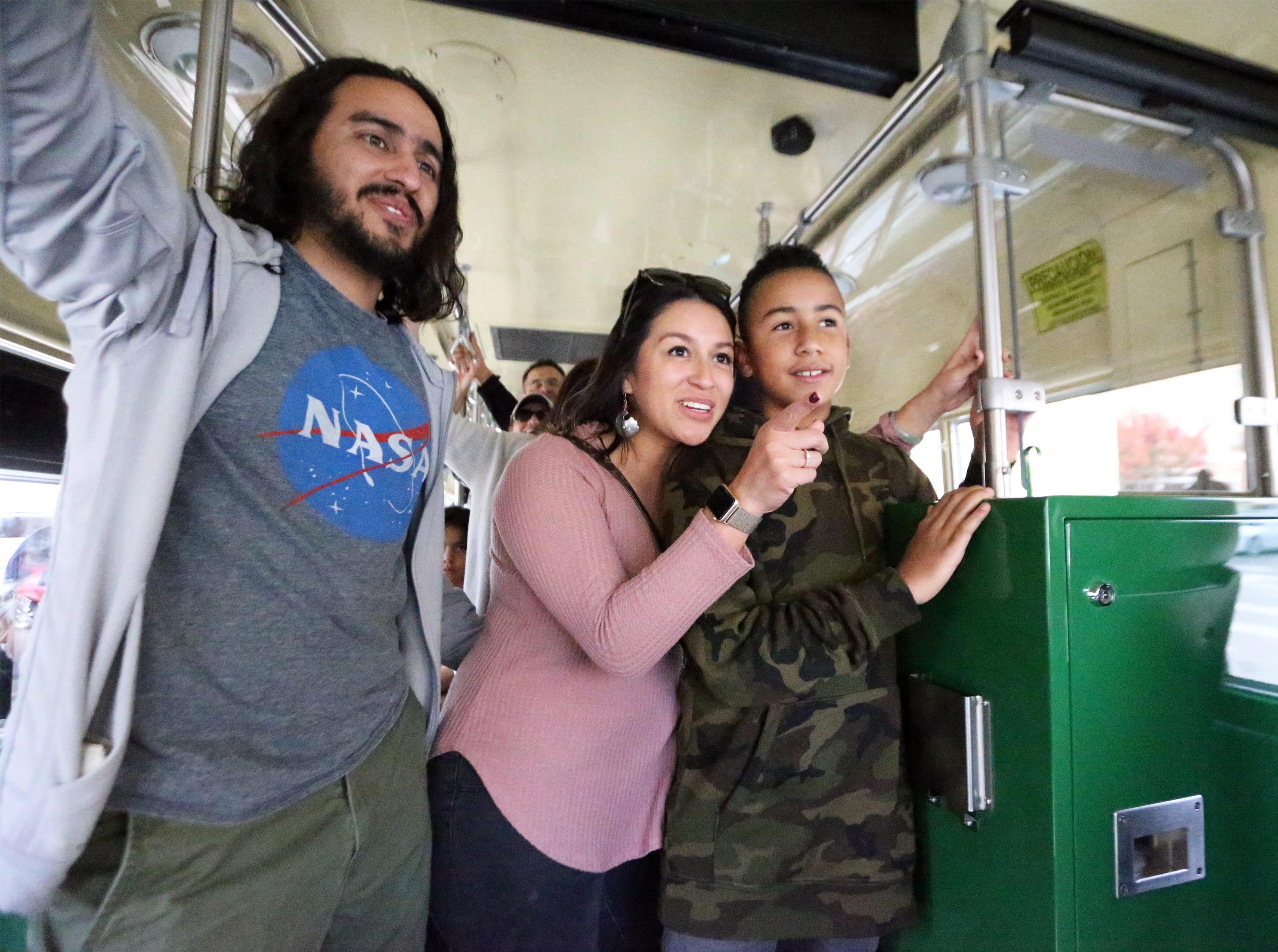Joksan Holguin, left, Angelica Hernandez and Diego Killingsworth ride a stading-room-only streetcar in the downtown area Friday afternoon.