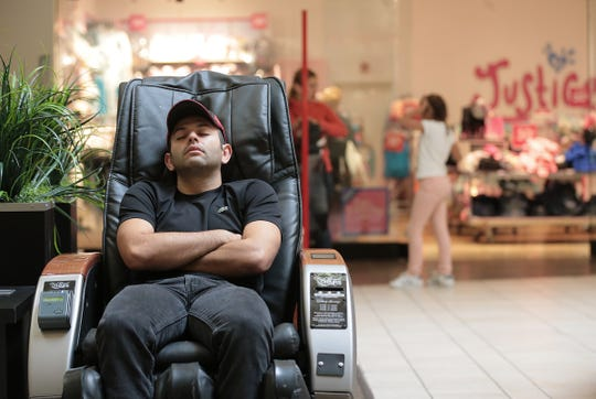 A man sleeps on a massage chair at Cielo Vista Mall Friday morning after the initial shopping rush ended.
