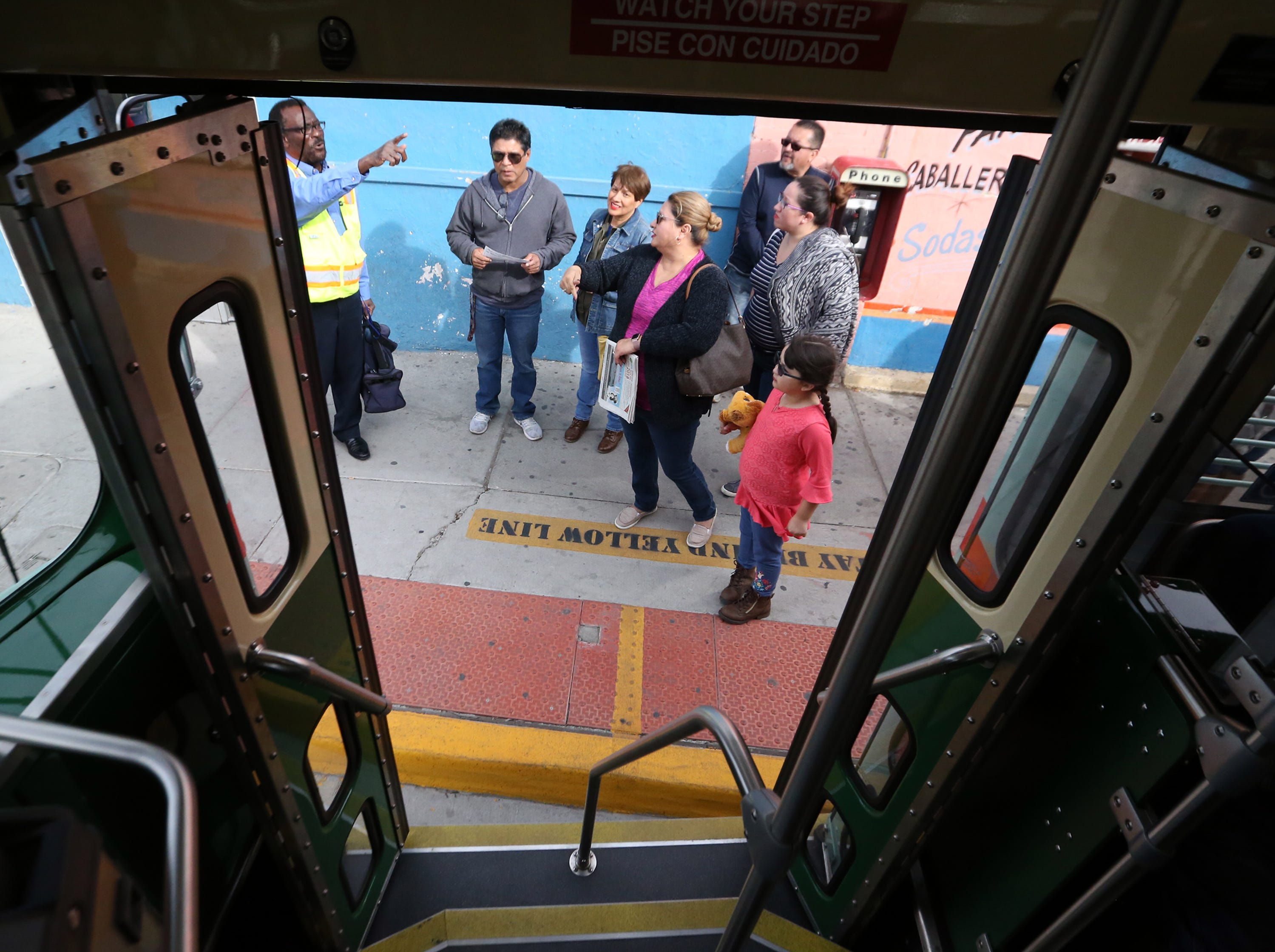 Light rail operator Victor Lawson, left, talks with passengers wishing to board Streetcar 1506 along Santa Fe Street in South El Paso Friday.