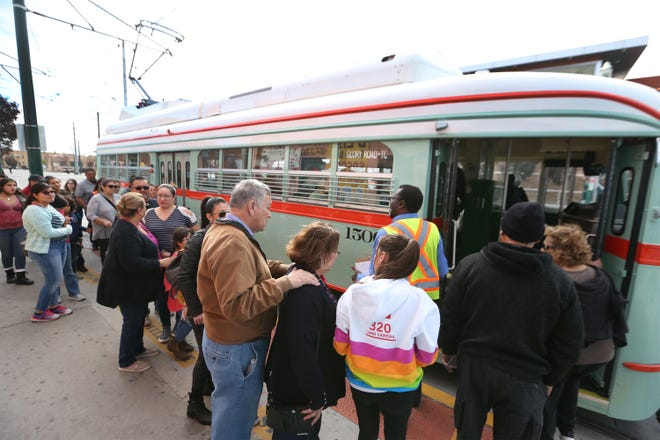 People line up to hop into streetcar 1506 along Santa Fe Street.