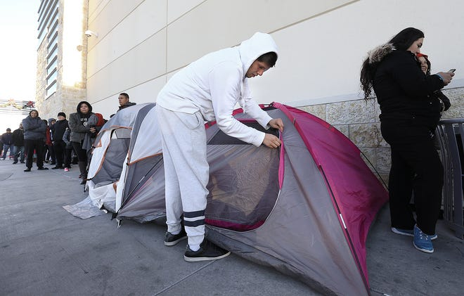 Fernando Jimenez zips up his tent after emerging from a horrible night's sleep outside Best Buy at The Fountains at Farah Friday morning. Jimenez was the first person in line.