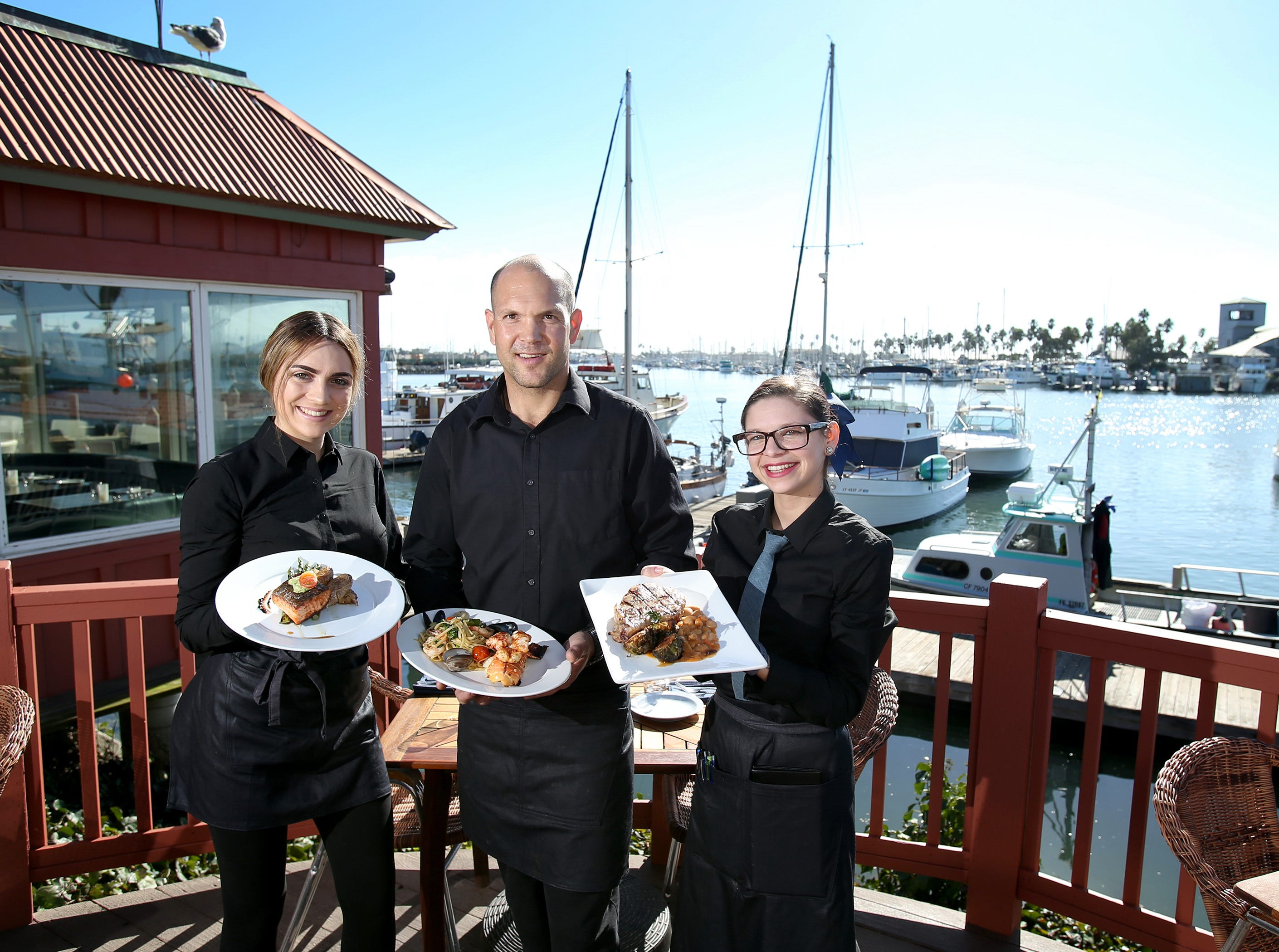 Water's Edge Restaurant and Bar's Hannah Fry (left to right), Brian Walters and Shawnna Rodriguez stand in the outdoor patio area of the new Ventura Harbor restaurant. Fry is holding the Crispy Skinned Salmon, Walters has the Mediterranean-Style Lobster Tail and Rodriguez has the Chipotle Orange-Glazed Pork Chop.