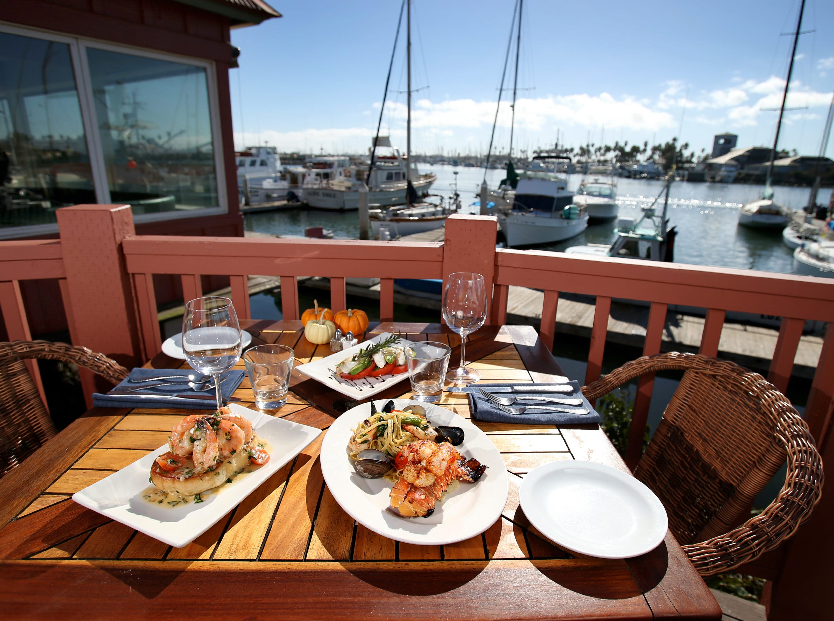 Water's Edge Restaurant and Bar is Ventura Harbor's newest waterfront restaurant. Pictured is its Garlic Shrimp Boat (left), Mediterranean-Style Lobster Tail and Cali-Prese Salad (back).
