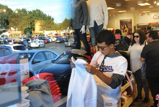 A Camarillo Premium Outlets parking lot is reflected in a store window as shoppers look for bargains on Black Friday.