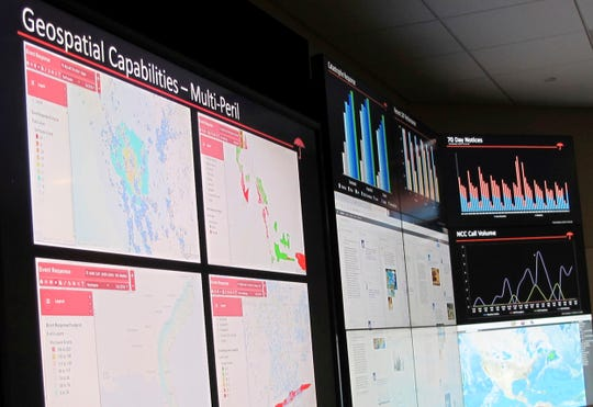 This Nov. 16 photo shows video monitors that display weather, social media and other data from natural disasters inside the Travelers catastrophe response command center in Windsor, Conn. The company uses the data to determine how to respond to disasters including the recent California wildfires.
