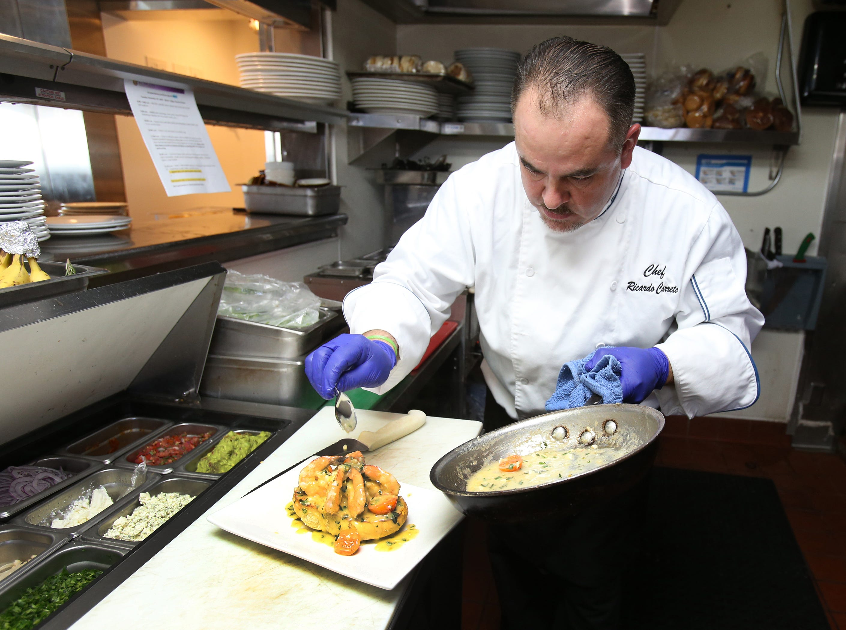Water's Edge Restaurant and Bar's Executive Chef Ricardo Carreto puts the final touches on his Garlic Shrimp Boat  at the new waterfront restaurant at the Ventura Harbor.