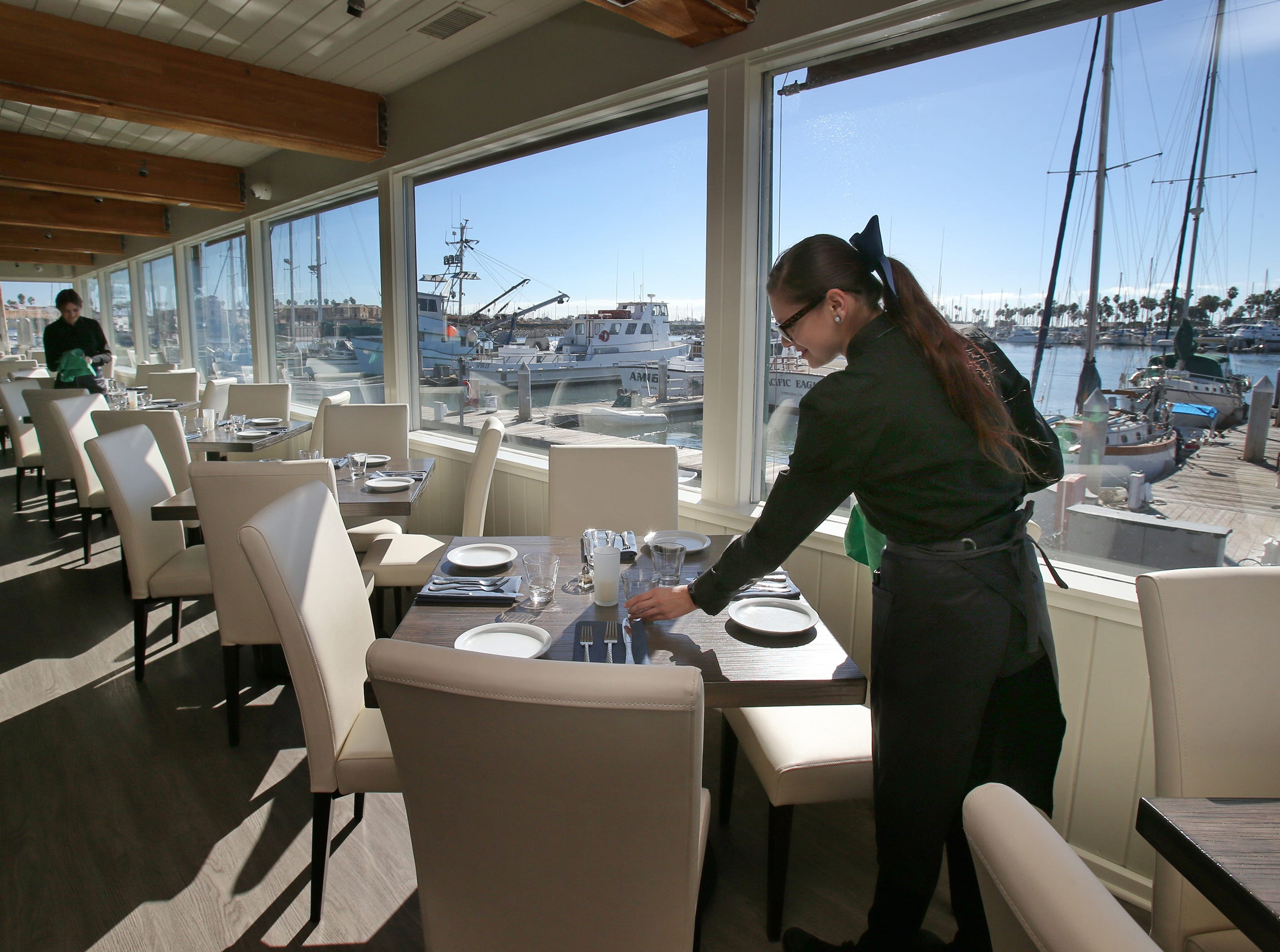Water's Edge Restaurant and Bar's Hannah Fry, left, and Shawnna Rodriguez prepare the main dining area of the new Ventura Harbor restaurant.