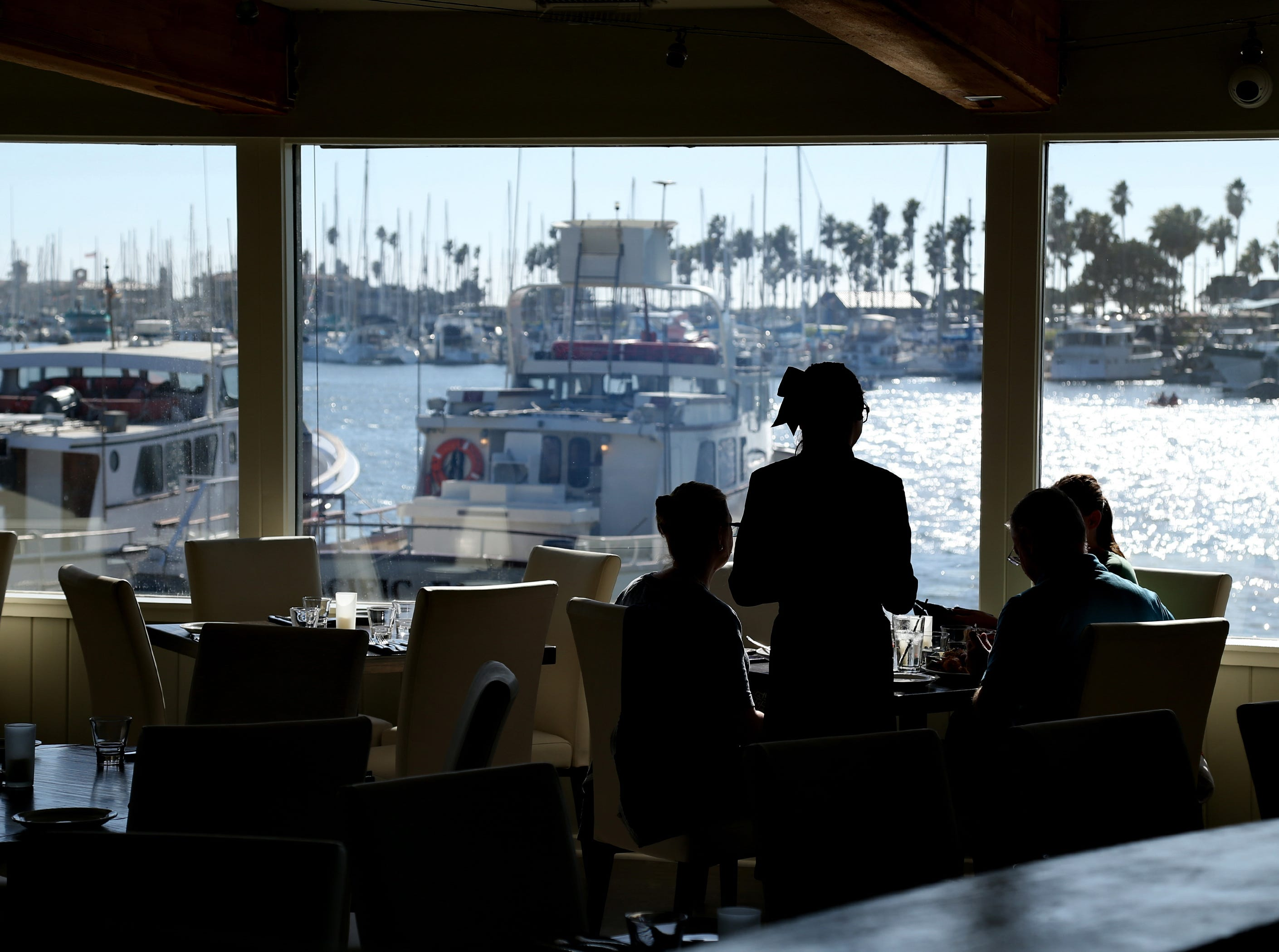 Water's Edge Restaurant and Bar's Shawnna Rodriguez helps diners at the new waterfront restaurant at the Ventura Harbor.