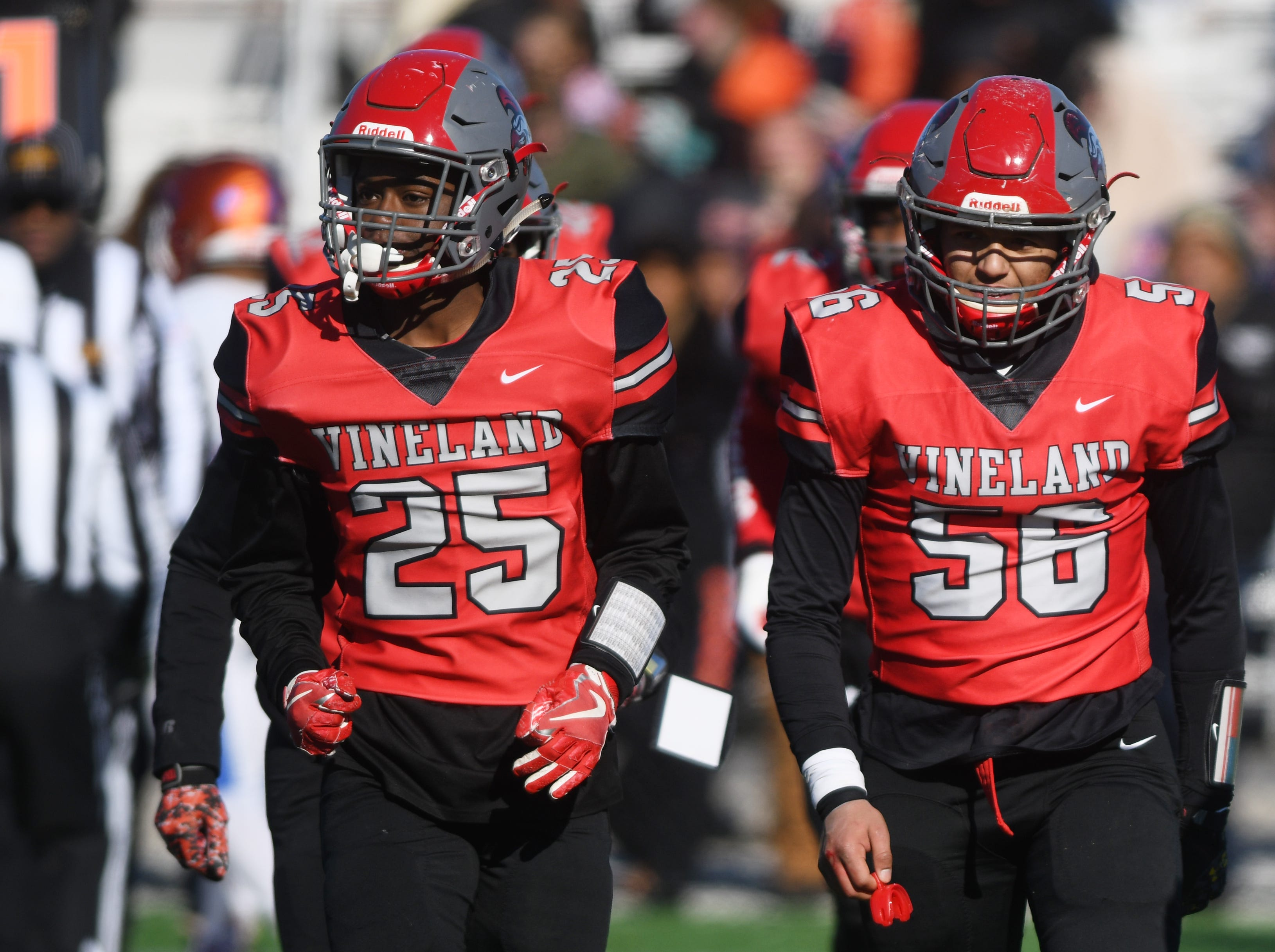 Vineland's Nayshaun Gregory (25) and Josue Delgado Jr. (56) head toward the sideline during a game against Millville at Gittone Stadium on Thanksgiving Day.
