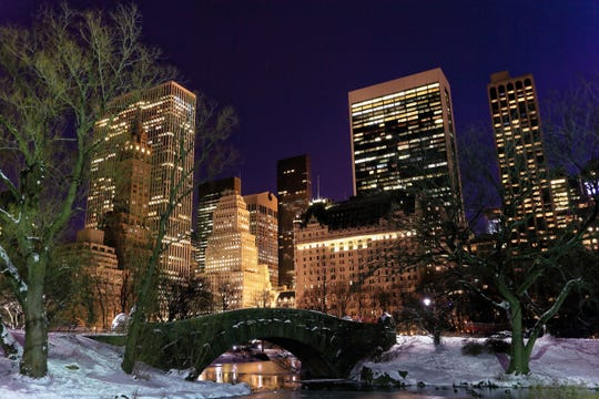 A snowy Central Park with The Plaza Hotel in the background.