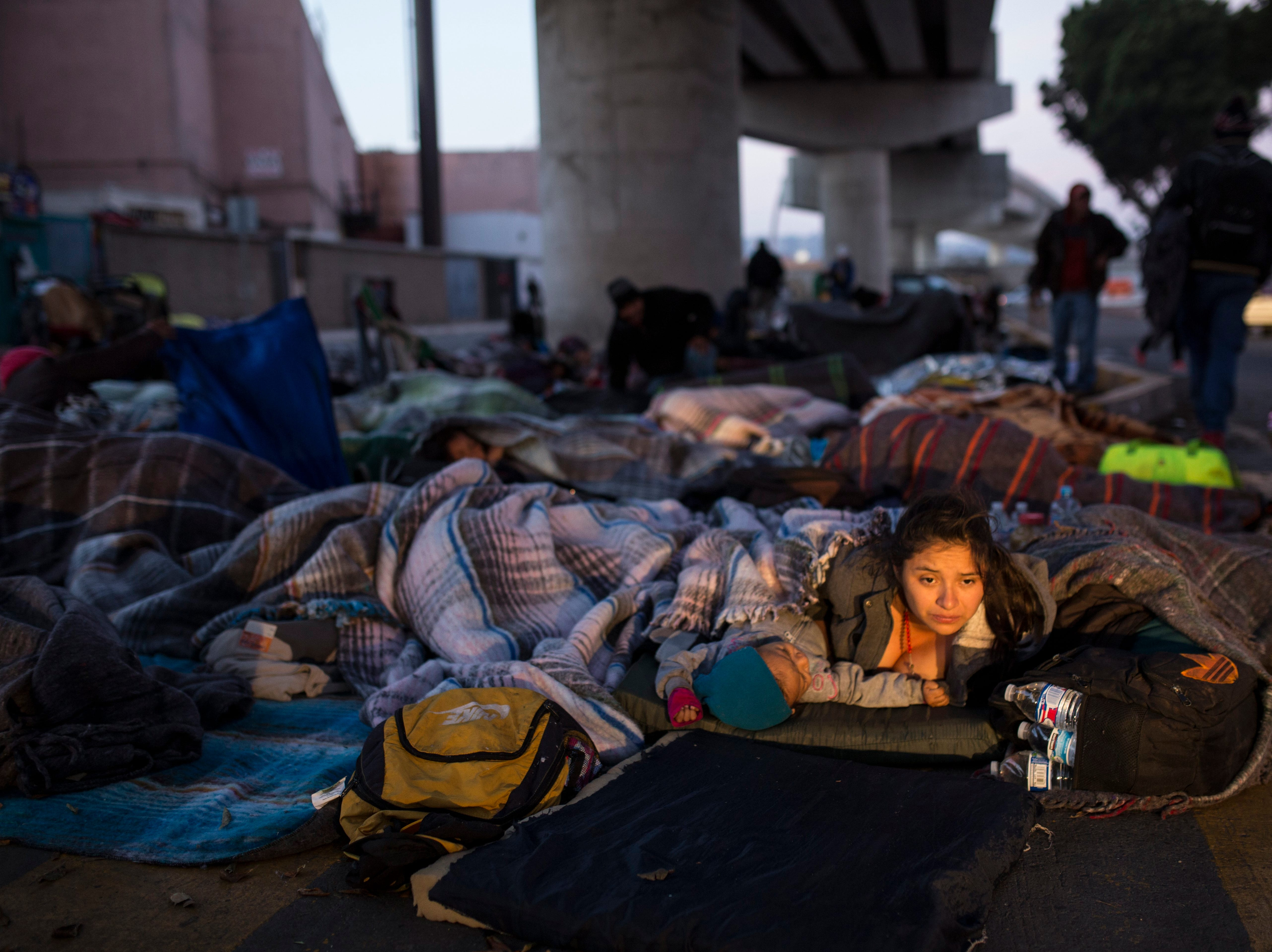 Early morning light illuminates the face of a migrant woman and her child as she wakes after sleeping under a bridge at the Chaparral border crossing in Tijuana, Mexico, Friday, Nov. 23, 2018.