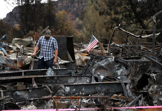 Noah Fisher looks over his home that was destroyed by the Camp Fire in Paradise, California.