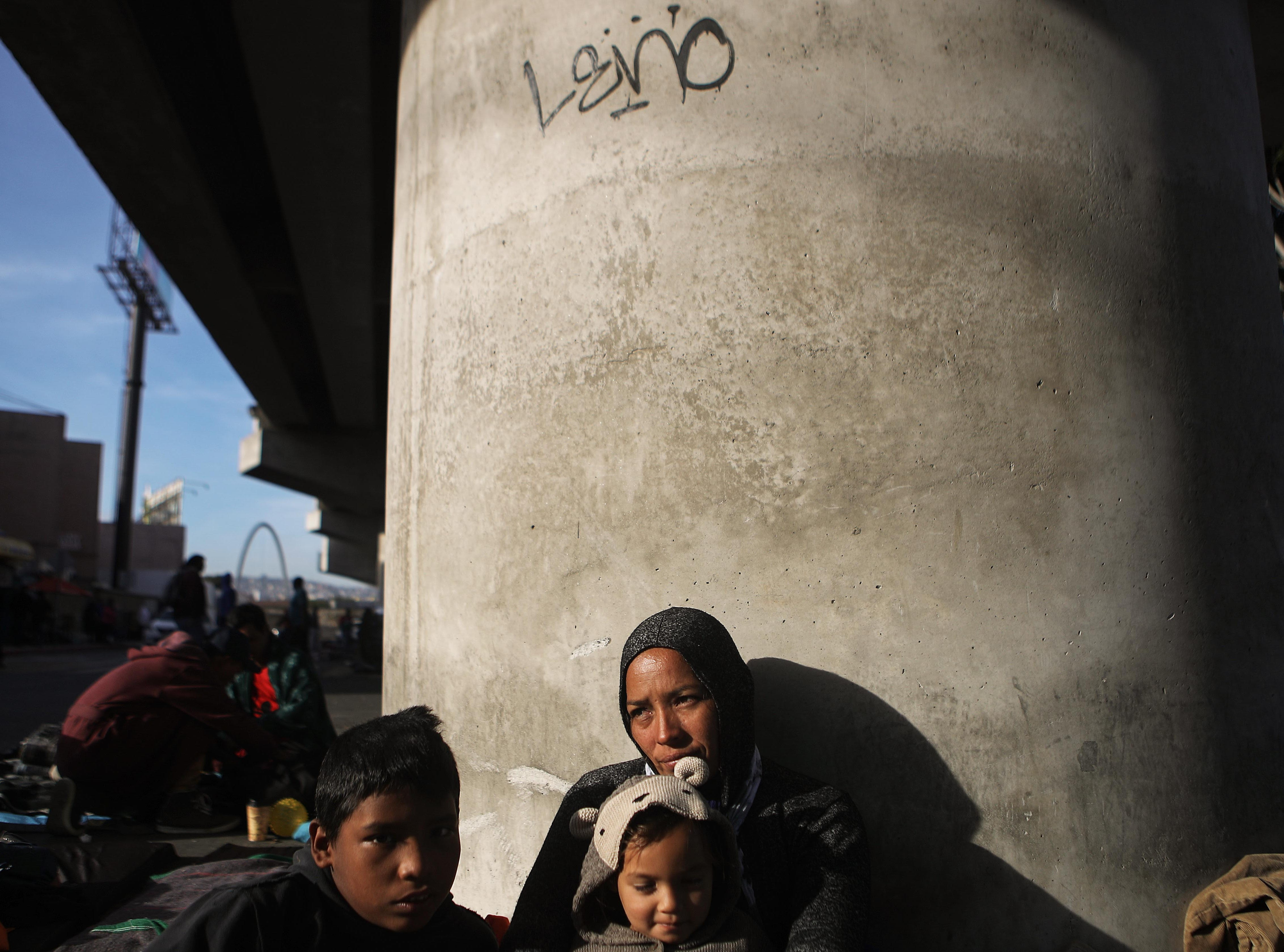 Honduran mother Lorena sits on the street with two of her four children, Yasir, left, and Maria, who all traveled together for more than one month in the 'migrant caravan', on Nov. 23, 2018 in Tijuana, Mexico.