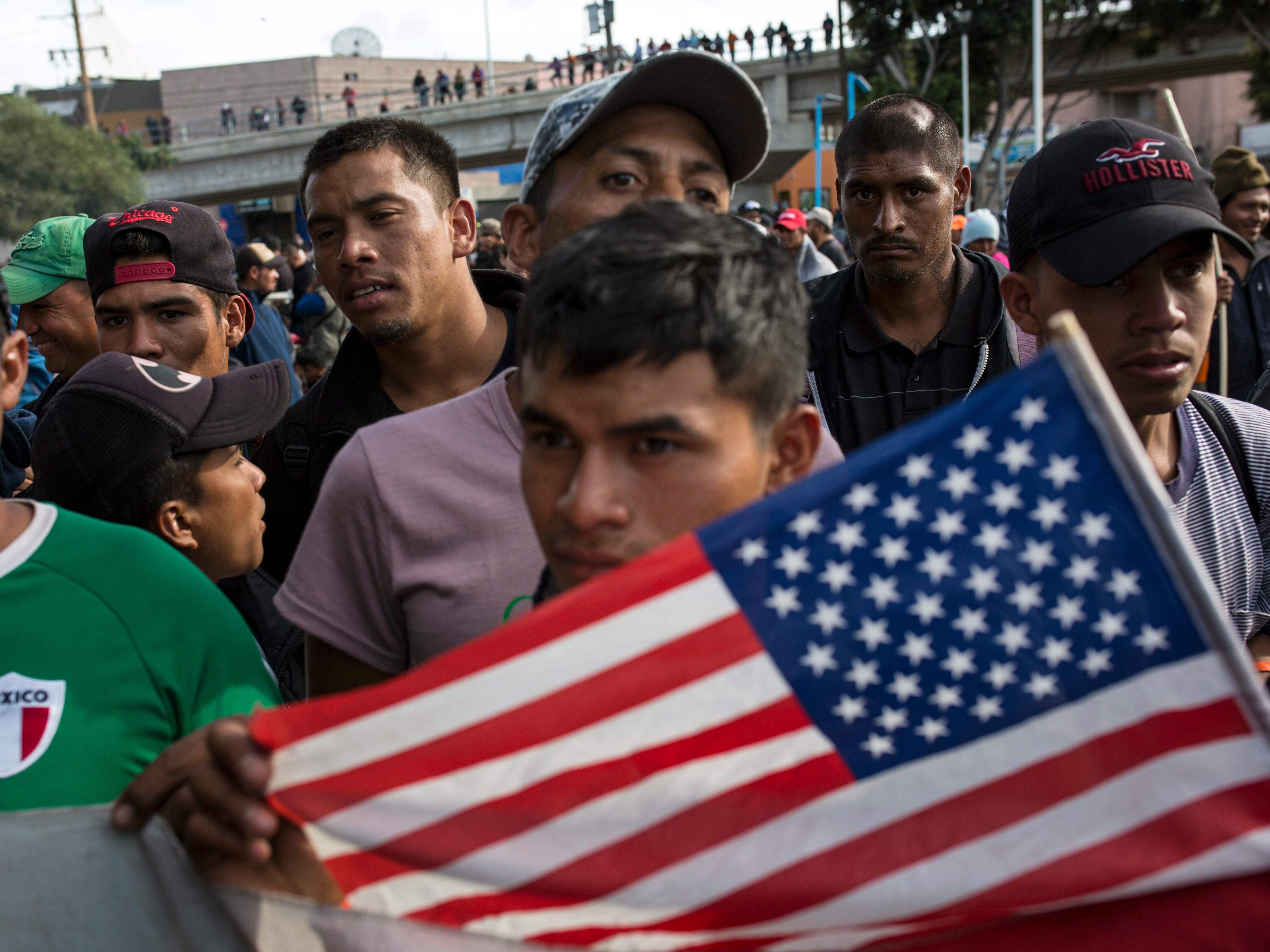 A migrant man holds a U.S. flag as he is confronted by a line of Mexican police in riot gear, when they tried to cross the border at the Chaparral border crossing in Tijuana, Mexico on Nov. 22, 2018. The group marched peacefully to the border crossing to demand better conditions and pushed to enter the U.S.