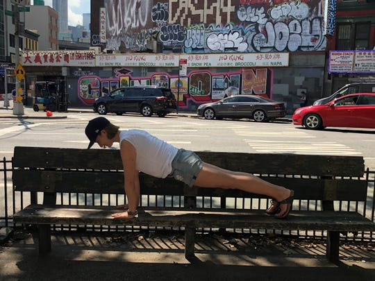 Erin Ranta moved to New York City last year. Now a Pilates instructor, she is shown doing the Pilates plank position in New York City's Chinatown in the summer of 2018.