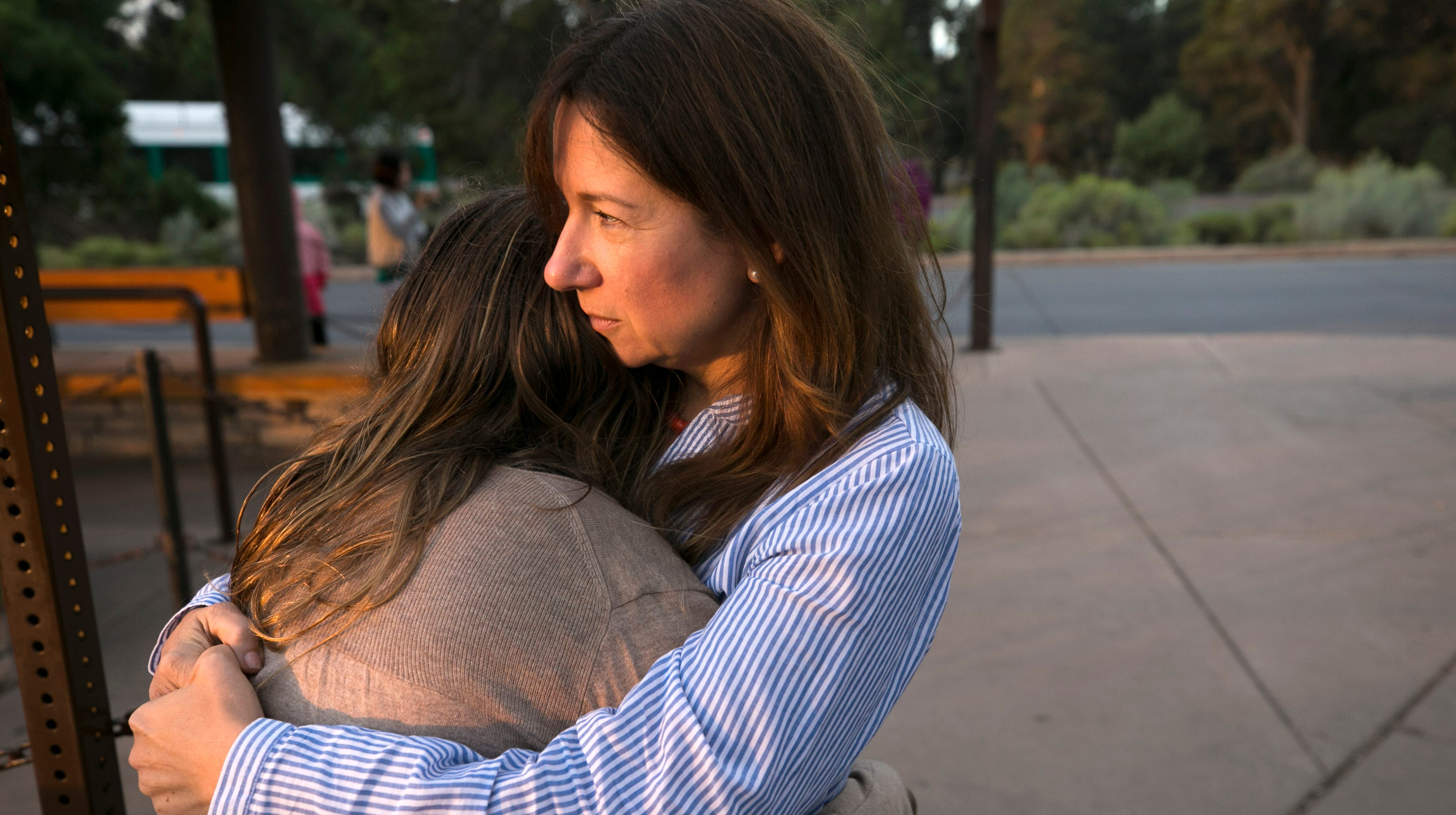 Laura Trujillo of Cincinnati, Ohio, and her daughter, Lucy Faherty, 12, hug while waiting for a Grand Canyon National Park shuttle bus to take them to the Trailview Overlook on the south rim of the Grand Canyon in Grand Canyon National Park.