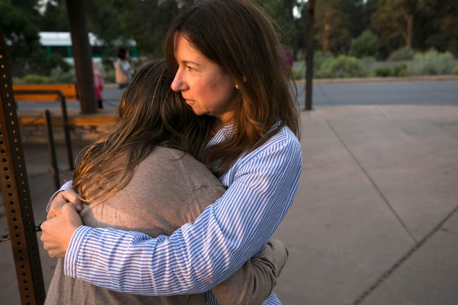 Laura Trujillo of Cincinnati and her daughter, Lucy Faherty, 12, hug while waiting for a Grand Canyon National Park shuttle bus to take them to the Trailview Overlook on the canyon's south rim.