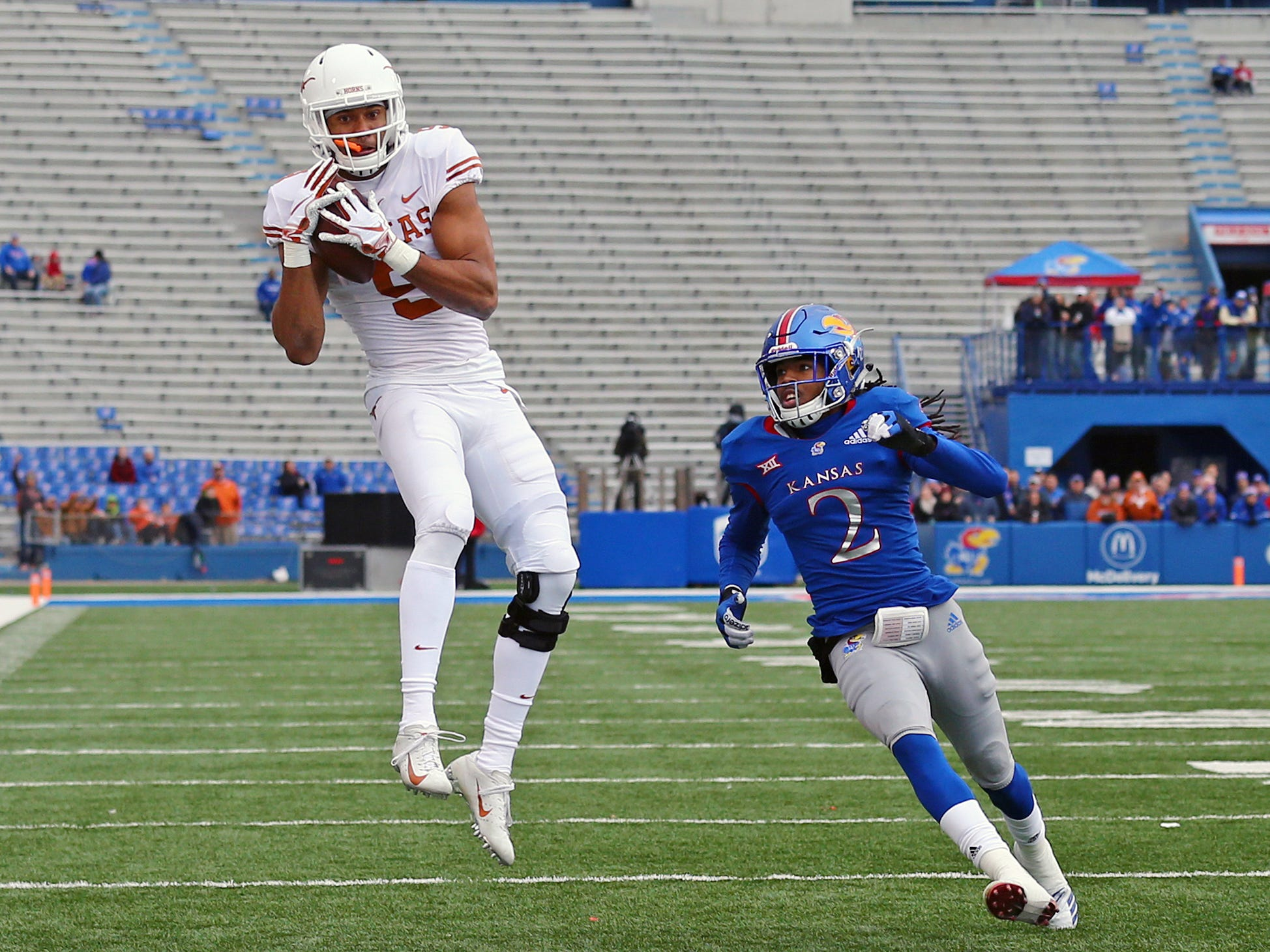 Texas wide receiver Collin Johnson (9) catches a pass for a touchdown against Kansas cornerback Corione Harris during the first half at Memorial Stadium.
