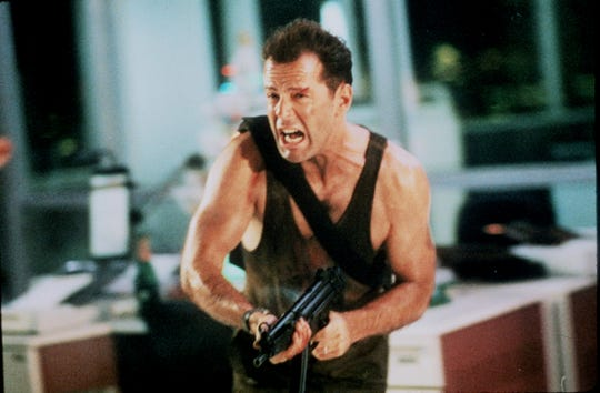 "John McClane (Bruce Willis) is forced to fend off terrorists who take a corporate holiday party hostage in ""Die Hard."""