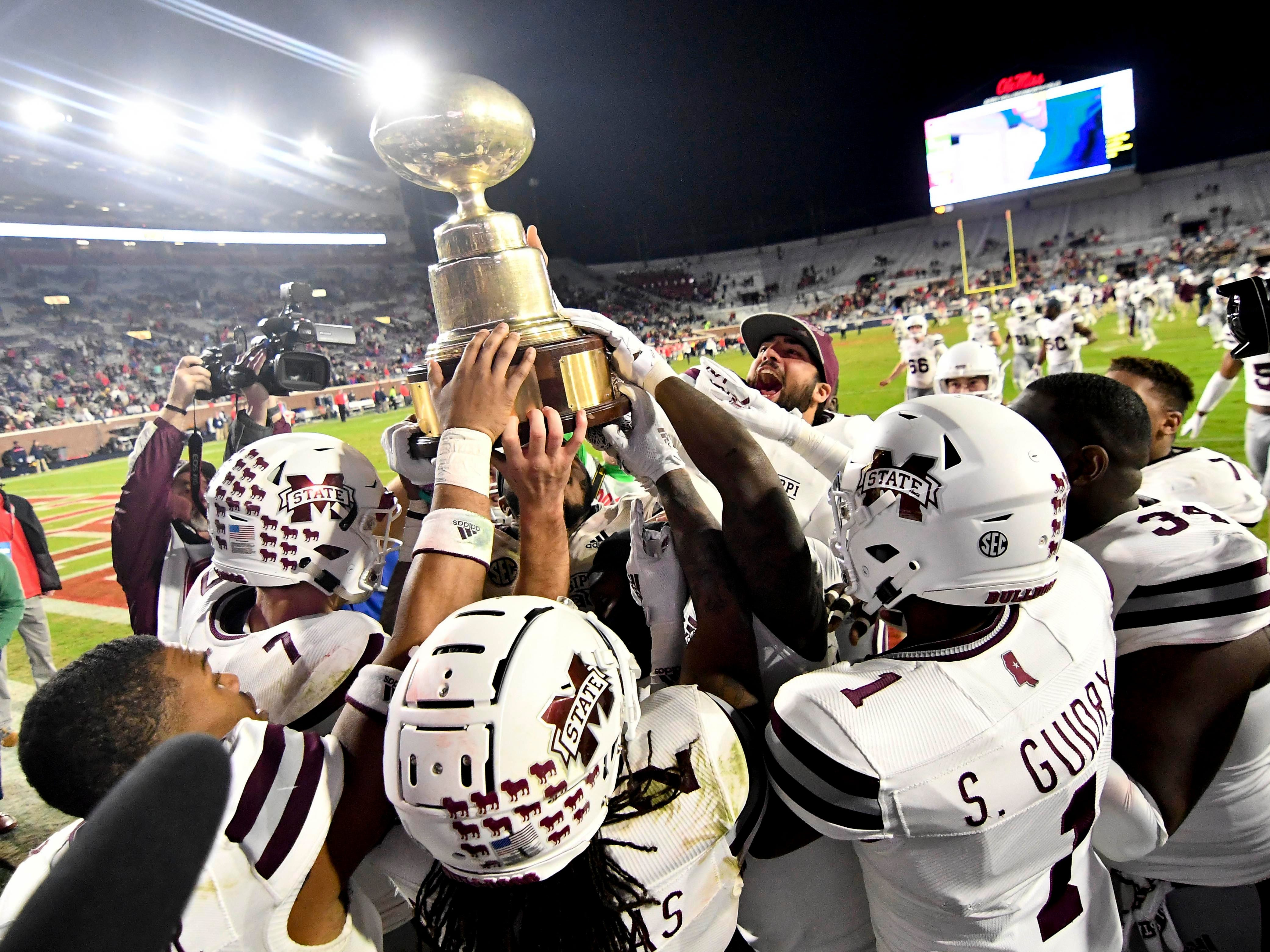 Mississippi State players celebrate with the Egg Bowl trophy after defeating Mississippi at Vaught-Hemingway Stadium.