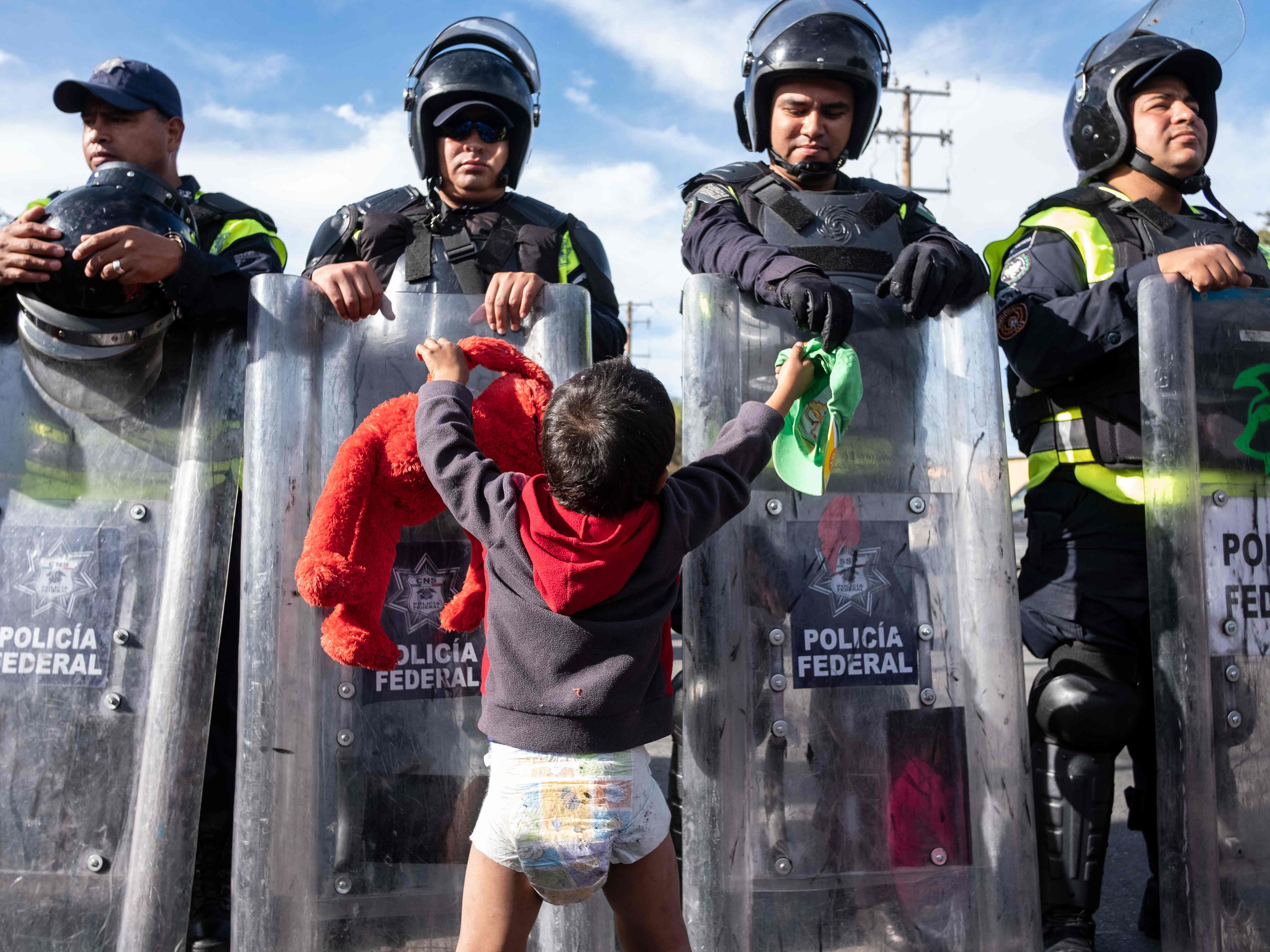 A migrant boy, part of the Central American migrants, plays with Mexico's Federal police at El Chaparral port of entry on the U.S.-Mexico border in Tijuana, Baja California state, Mexico on Nov. 22, 2018