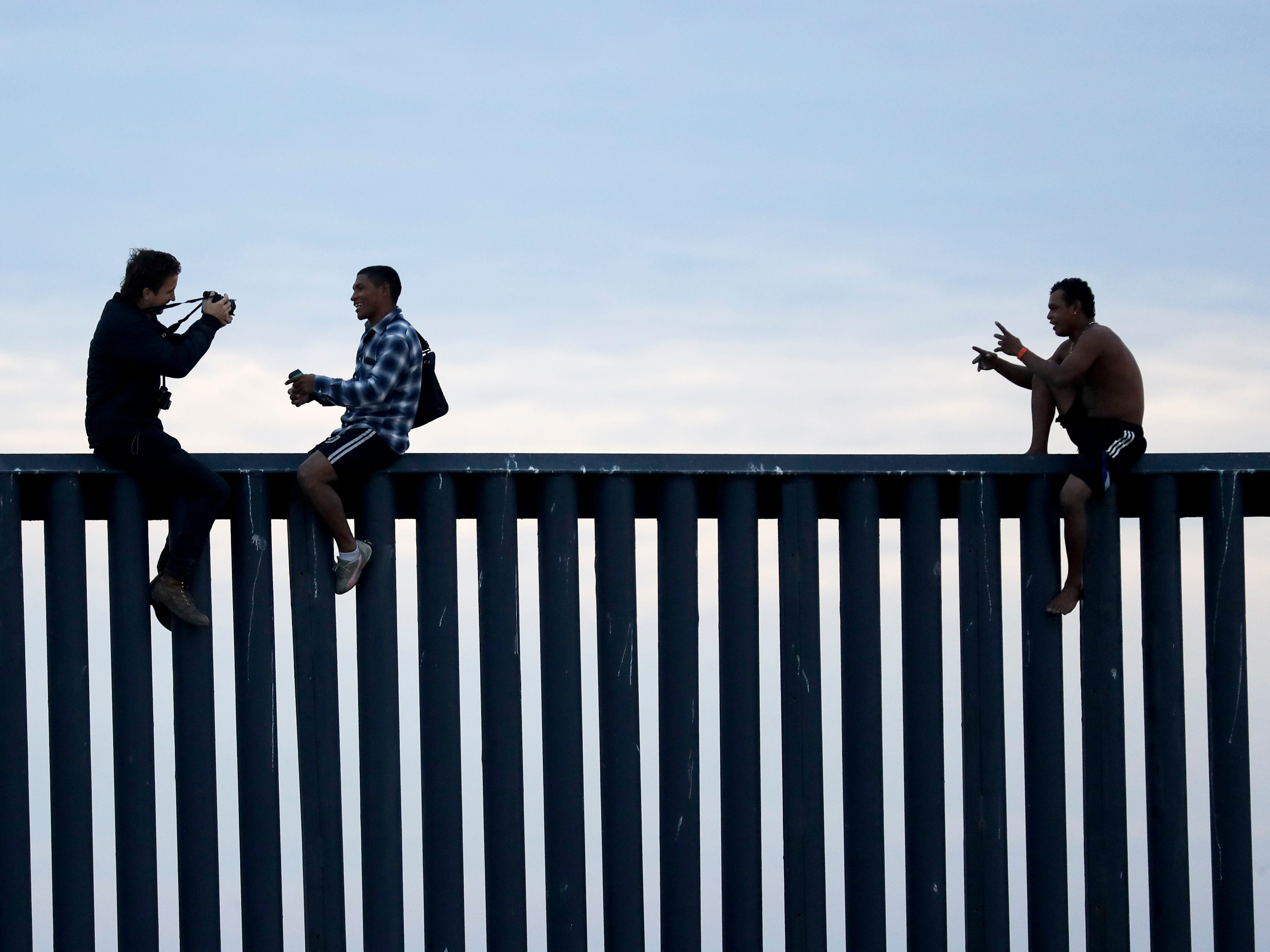 Two Honduran men pose as a photographer, at left, takes their picture after the group climbed the border wall separating Tijuana, Mexico, and San Diego, before climbing back down on the Mexican side on Nov. 21, 2018 as seen from San Diego.
