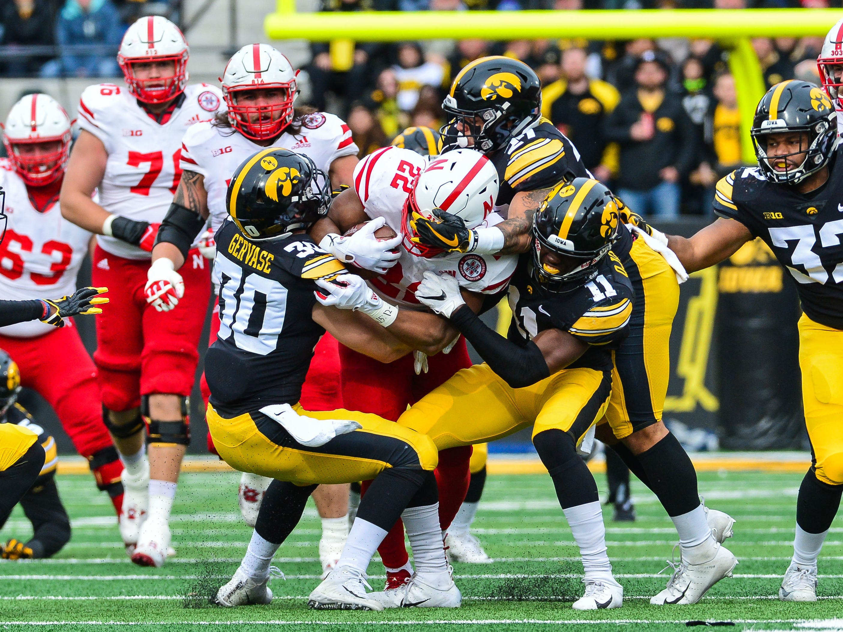 Nebraska running back Devine Ozigbo  is tackled by a group of Iowa defenders during the second quarter at Kinnick Stadium.