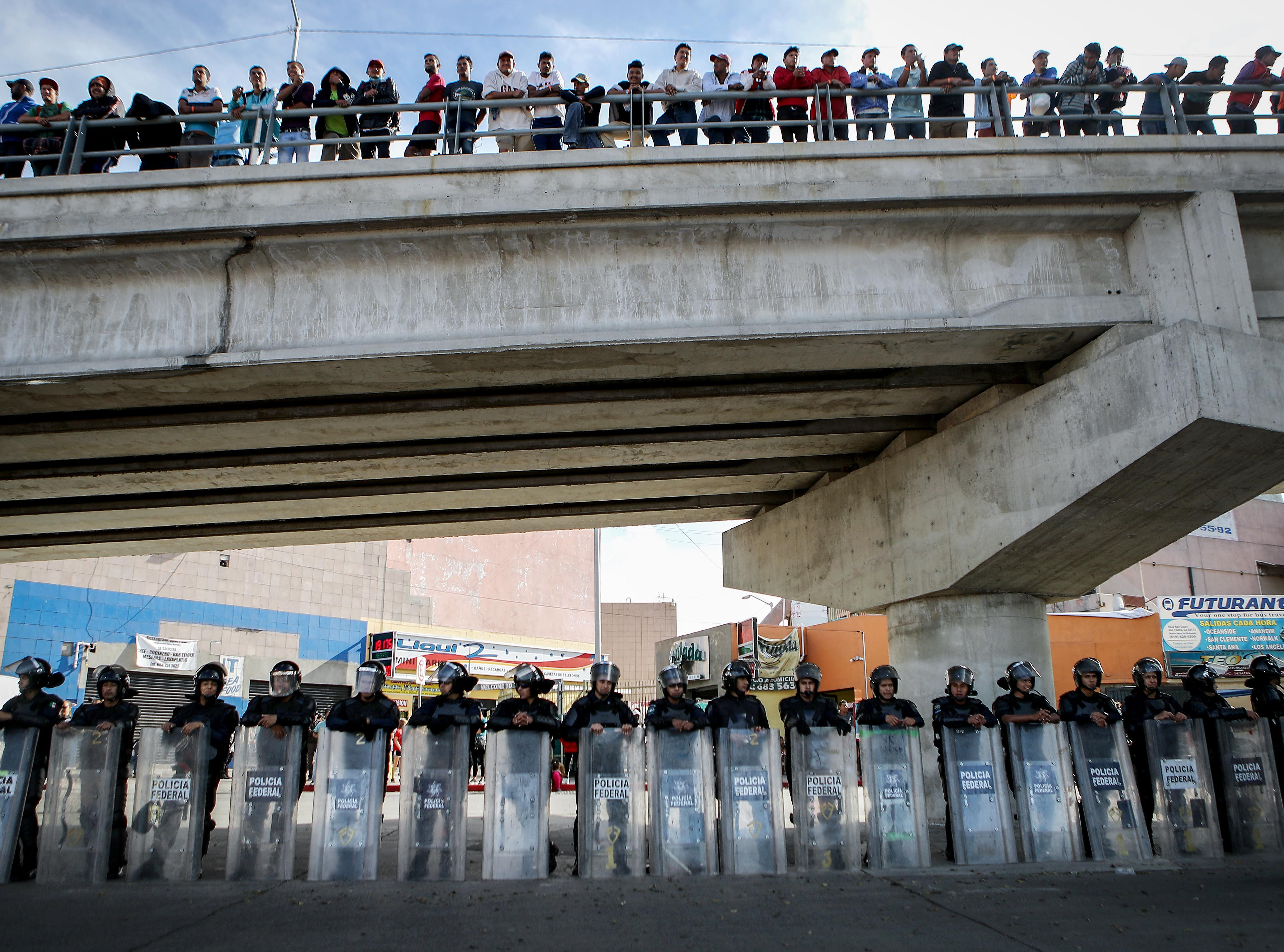 Mexican riot police keep watch beneath onlookers on a bridge as members of the 'migrant caravan' rally outside the El Chaparral port of entry on Nov. 22, 2018 in Tijuana, Mexico. Parts of the migrant caravan have been arriving to Tijuana after traveling for more than a month through Central America and Mexico to reach the U.S. border. President Donald Trump today threatened to close the U.S.-Mexico border if the arrival of migrants leads to a loss of 'control' on the Mexican side.