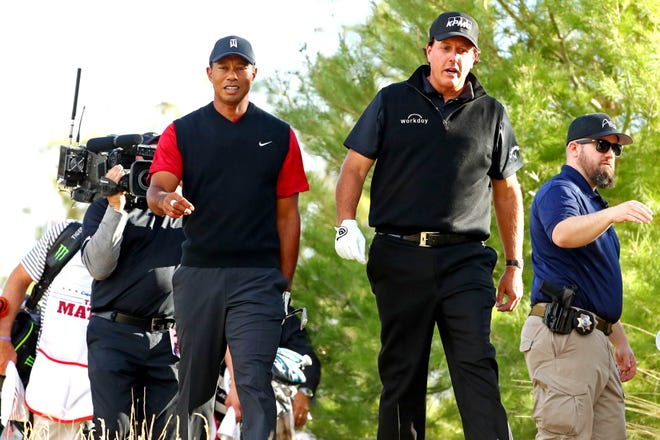 Tiger Woods and Phil Mickelson walk off the ninth tee.