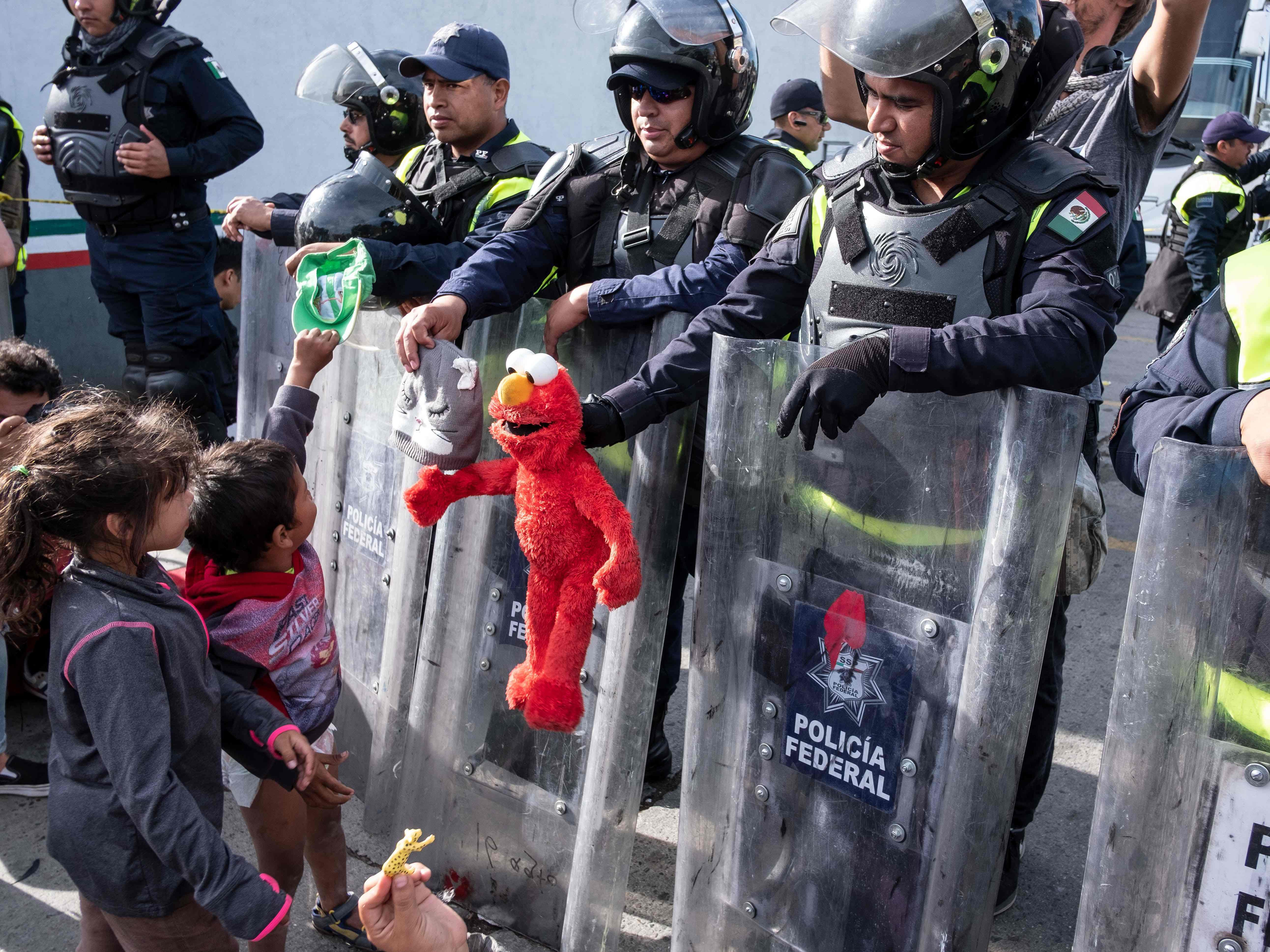Migrant children, part of the Central American migrants, play with Mexico's Federal police at El Chaparral port of entry on the U.S.-Mexico border in Tijuana, Baja California state, Mexico on Nov. 22, 2018.