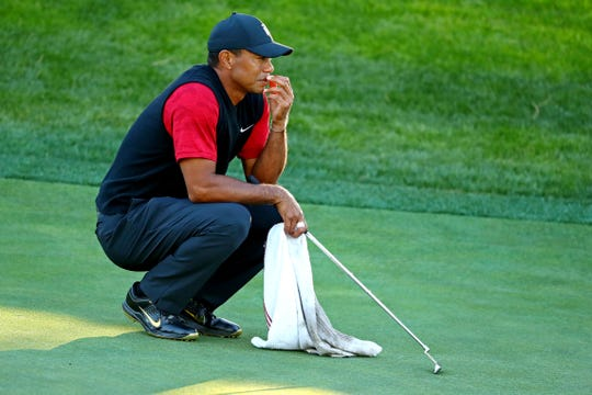 Tiger Woods lines up a putt on the 14th green.