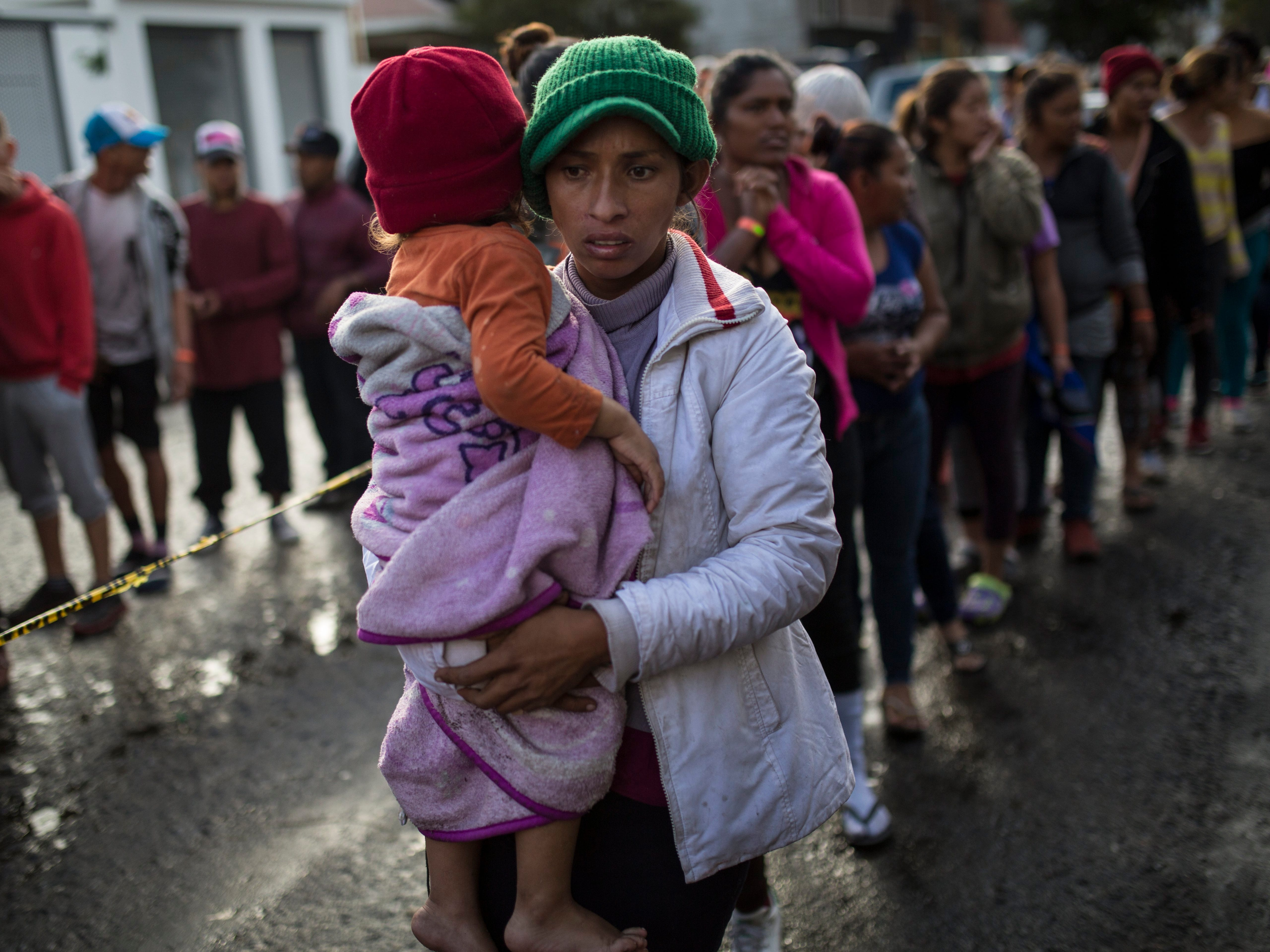 Maria del Carmen Mejia holds her daughter Britany Sofia while standing in a line outside a migrant shelter in Tijuana, Mexico, on Nov. 22, 2018.