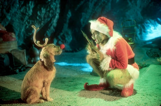 Jim Carrey, like the Grinch, with Max, in a scene from 2000