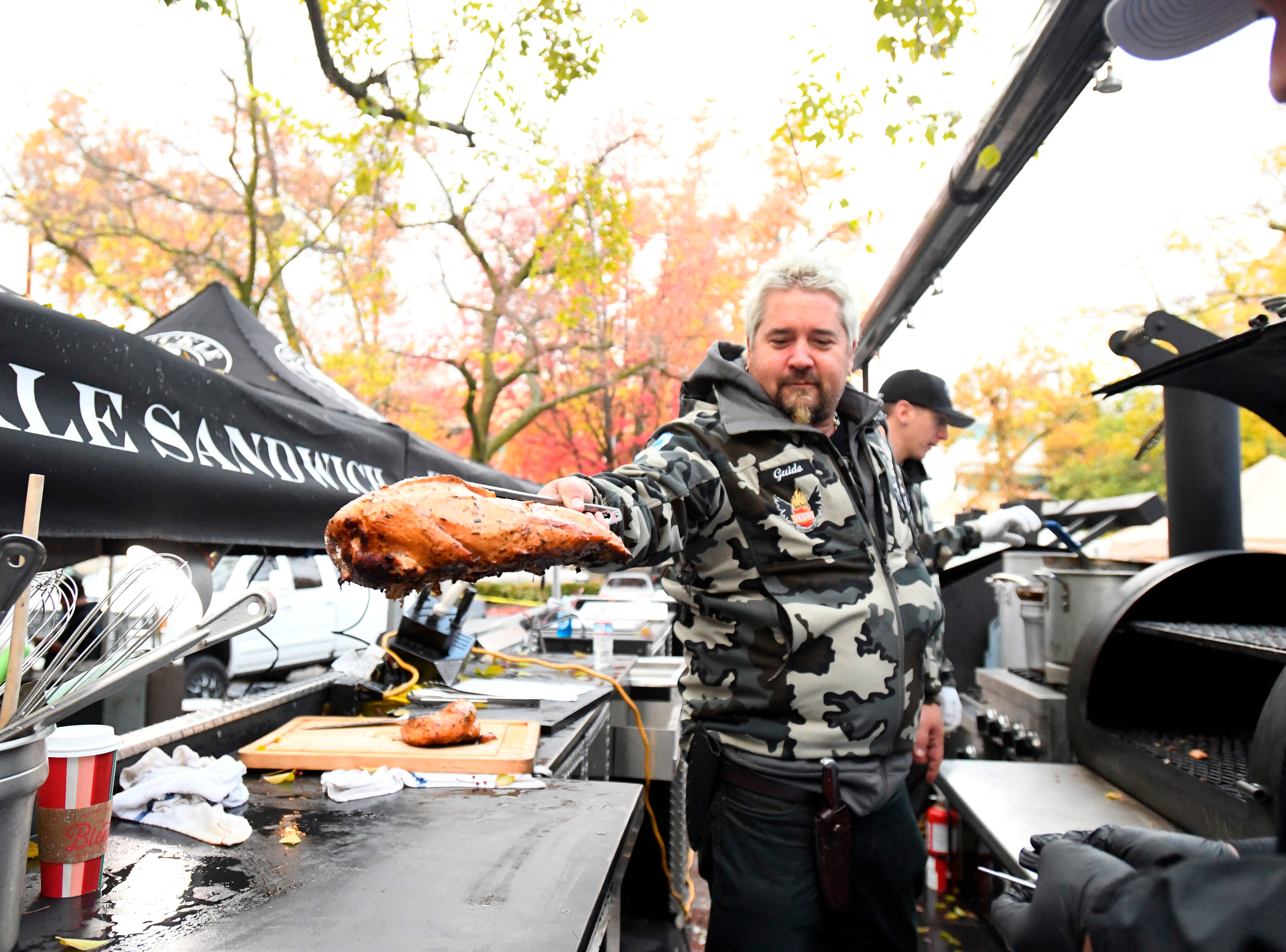 Chef Guy Fieri pulls a turkey from a grill, Thursday, Nov. 22, 2018, in Chico, Calif. Fieri was among the volunteers who showed up to prepare Thanksgiving meals for evacuees from the Camp Fire, which devastated the nearby town of Paradise, Calif. (Benjamin Spillman/The Reno Gazette-Journal via AP) ORG XMIT: NVREN401