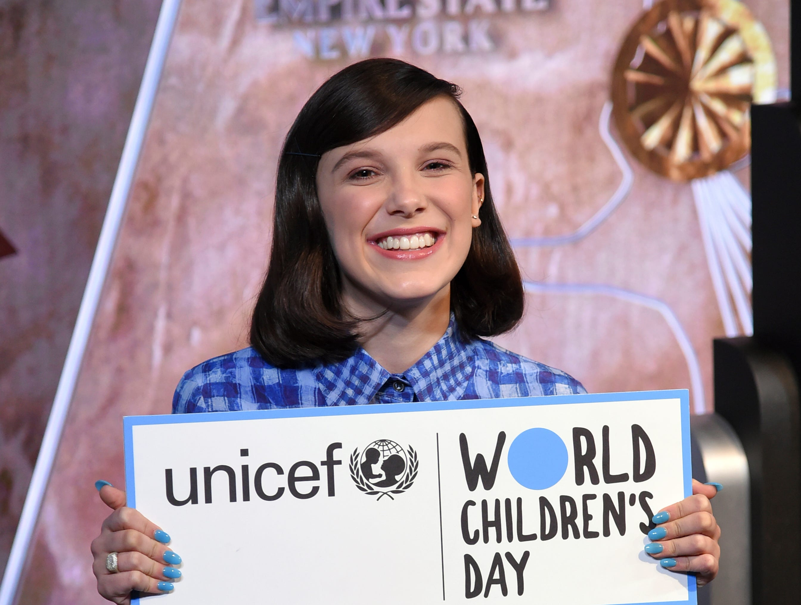 Actress Millie Bobby Brown holds a sign for UNICEF's World Children's Day as she attends a ceremonial lighting of the Empire State Building on Tuesday, Nov. 20, 2018, in New York. (Photo by Evan Agostini/Invision/AP) ORG XMIT: NYEA102