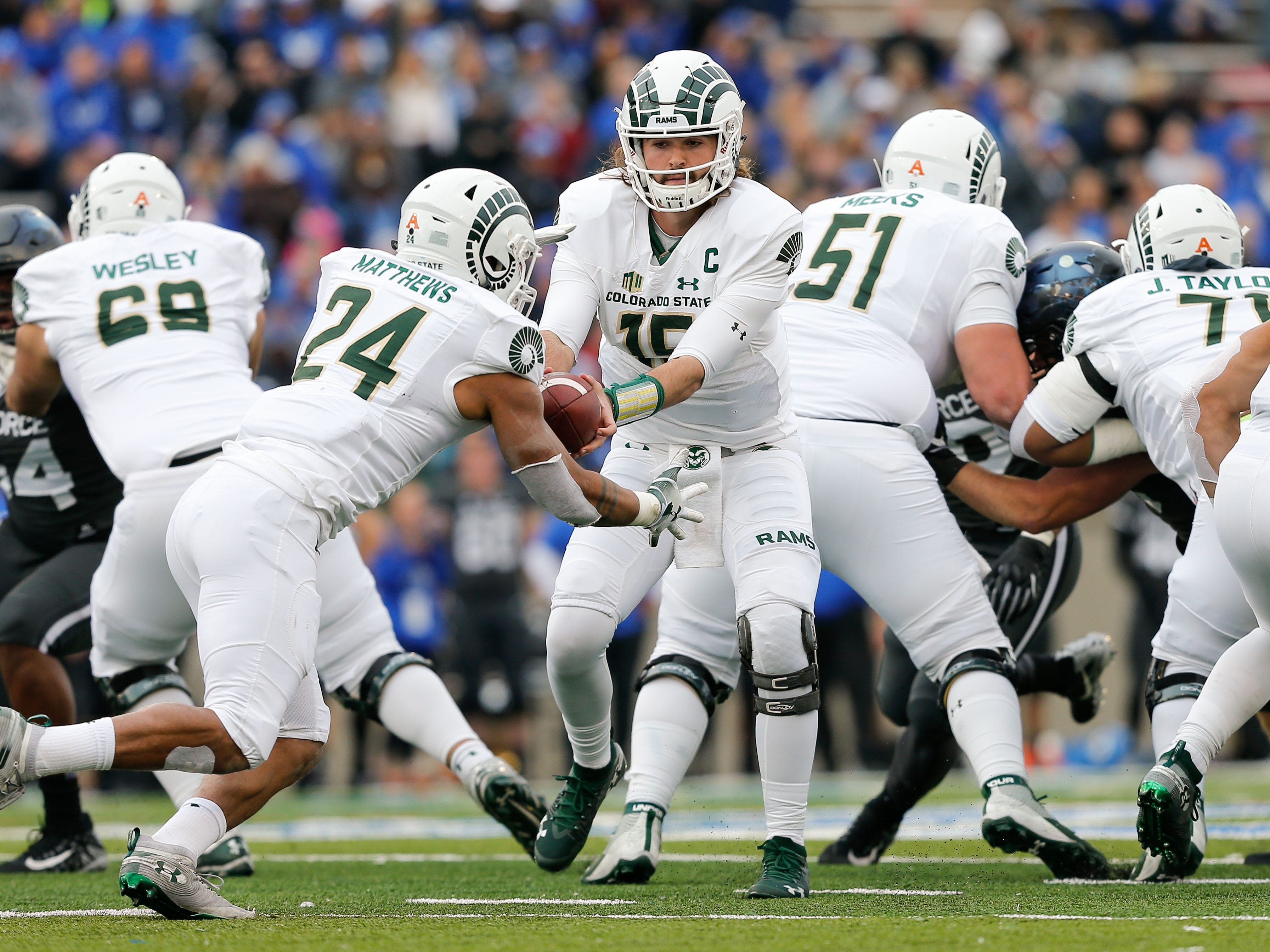 Colorado State quarterback Collin Hill  hands the ball off to running back Izzy Matthews during their game against Air Force.