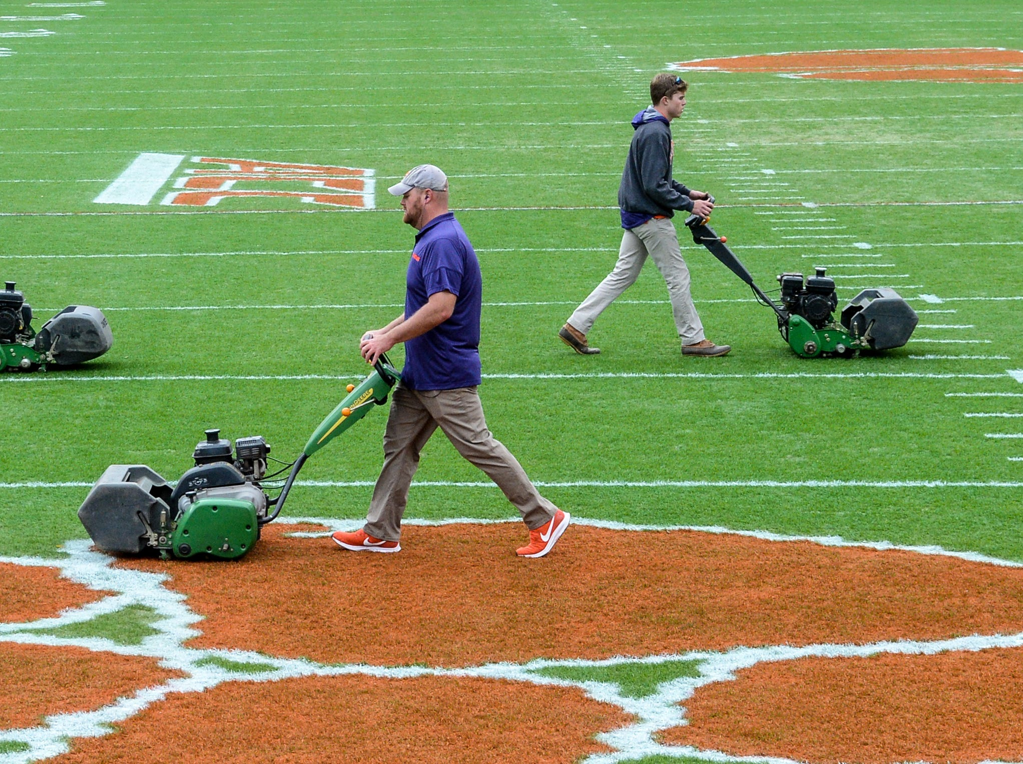 Dan McKinney, middle, Clemson University Athletic Grounds, coworkers Philip Rhodes, left, and Marshall Wagner run grass trimming machines over the field seven hours before kickoff in Memorial Stadium, before the South Carolina at Clemson football game in Clemson on Saturday, November 24, 2018.