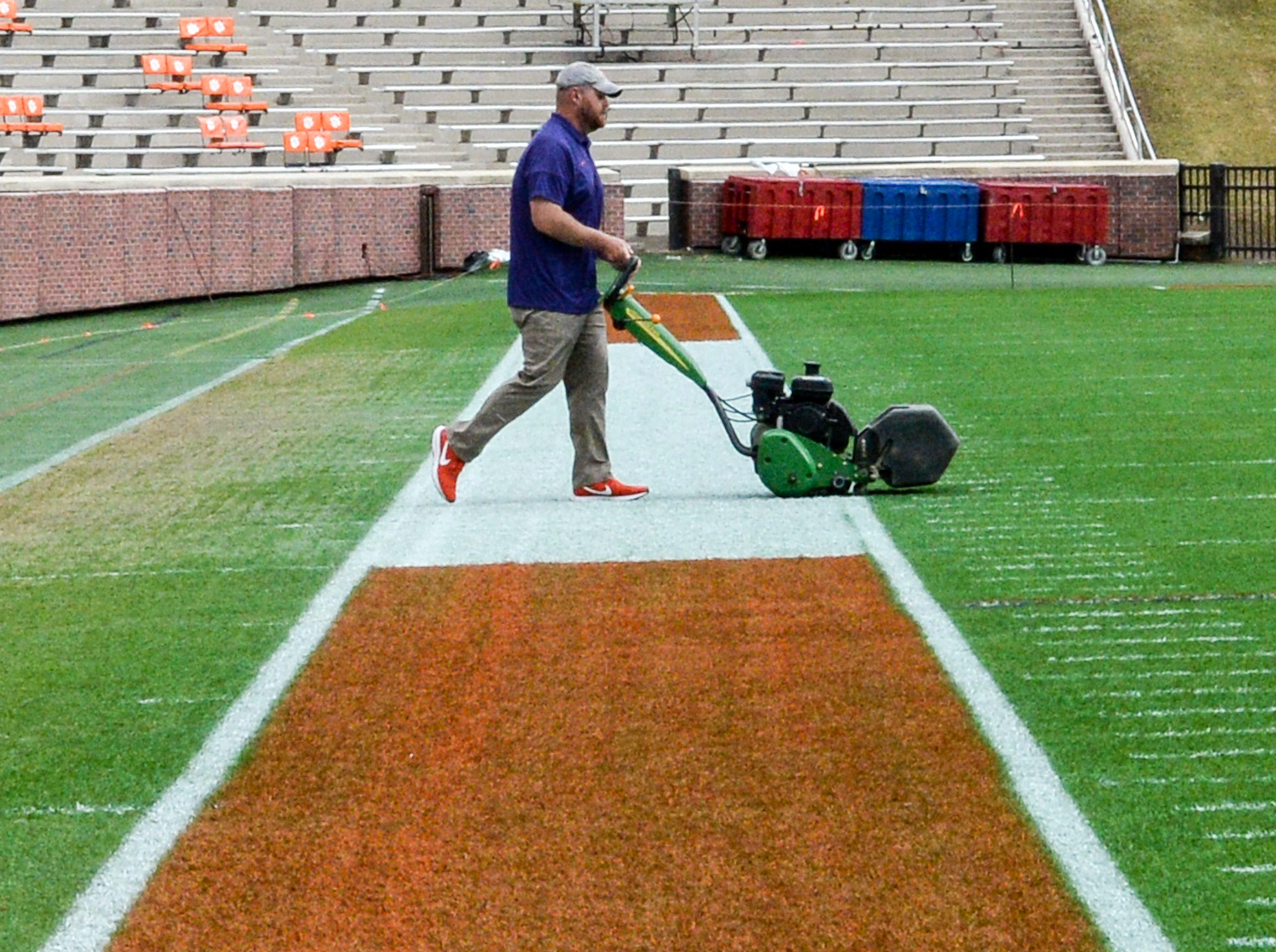 Dan McKinney, Clemson University Athletic Grounds, runs a grass trimming machine over the field seven hours before kickoff in Memorial Stadium, before the South Carolina at Clemson football game in Clemson on Saturday, November 24, 2018.