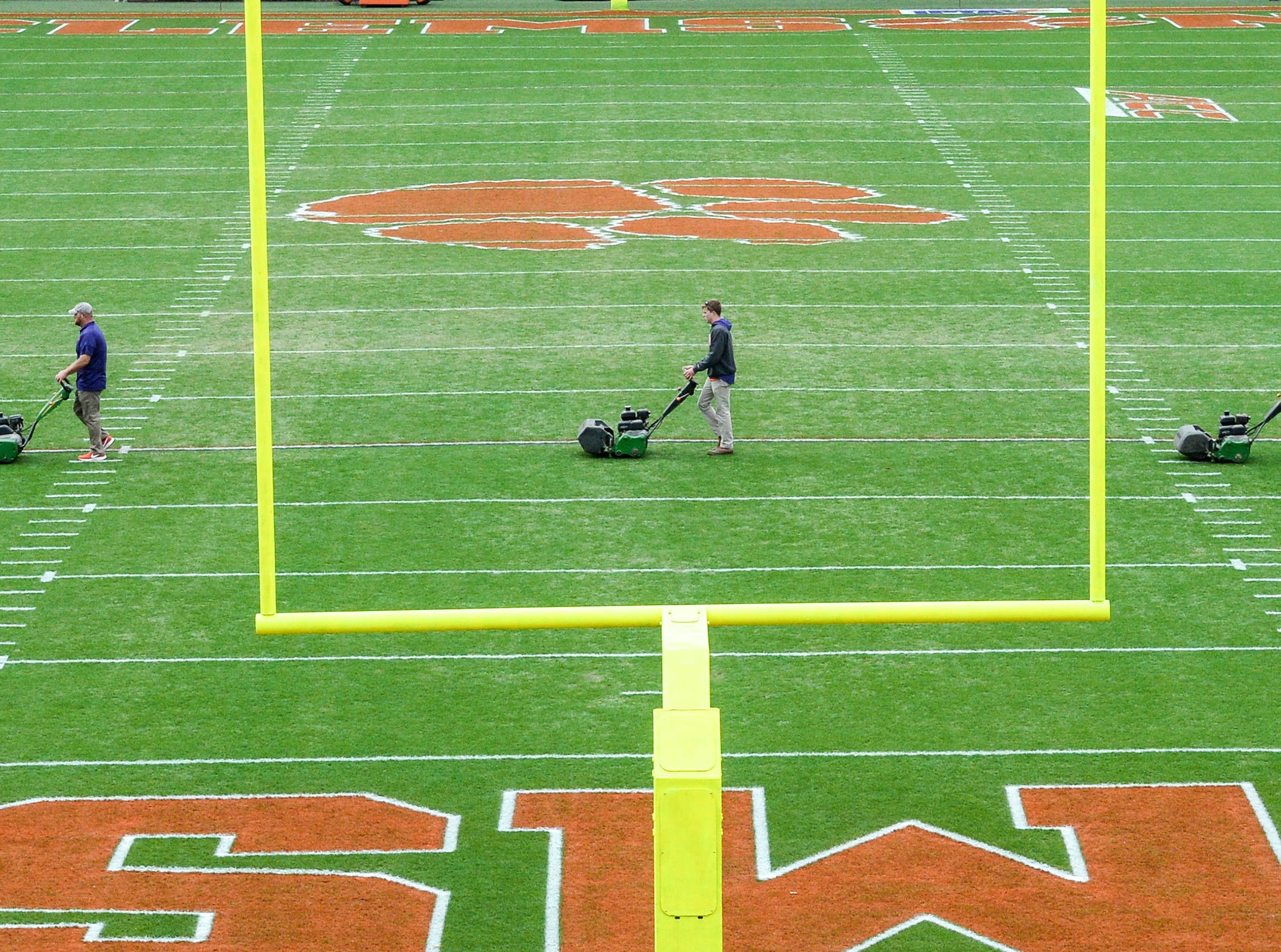 Dan McKinney, left, Clemson University Athletic Grounds, and coworkers Philip Rhodes, middle, and Marshall Wagner run a grass trimming machine over the field seven hours before kickoff in Memorial Stadium, before the South Carolina at Clemson football game in Clemson on Saturday, November 24, 2018.
